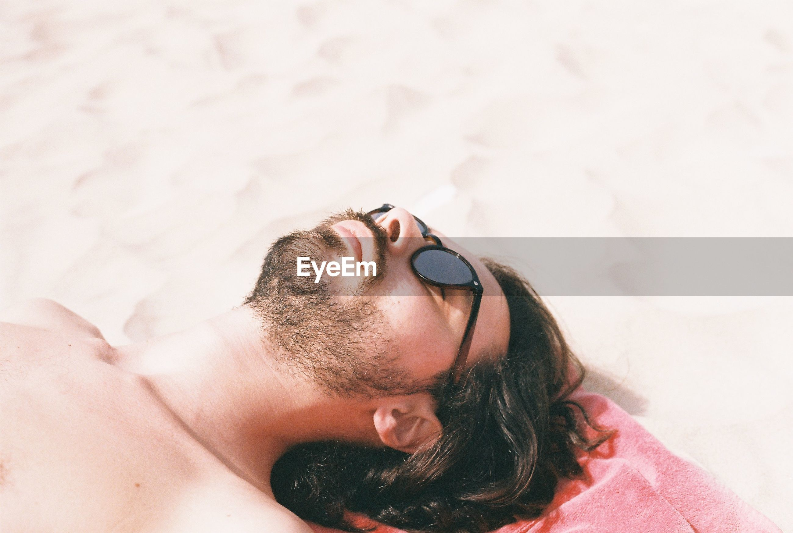 High angle view of shirtless young man lying on sand at beach during sunny day