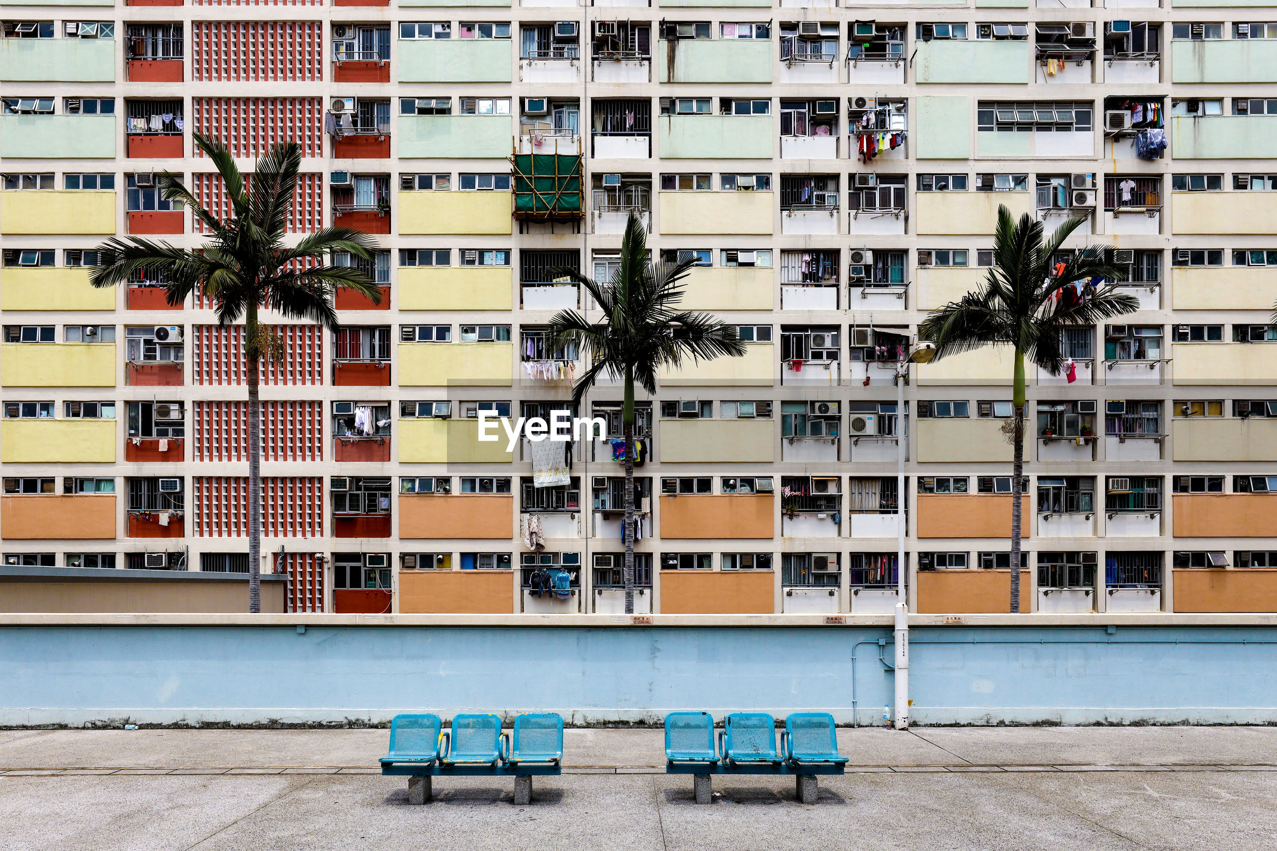 Empty benches against colorful building