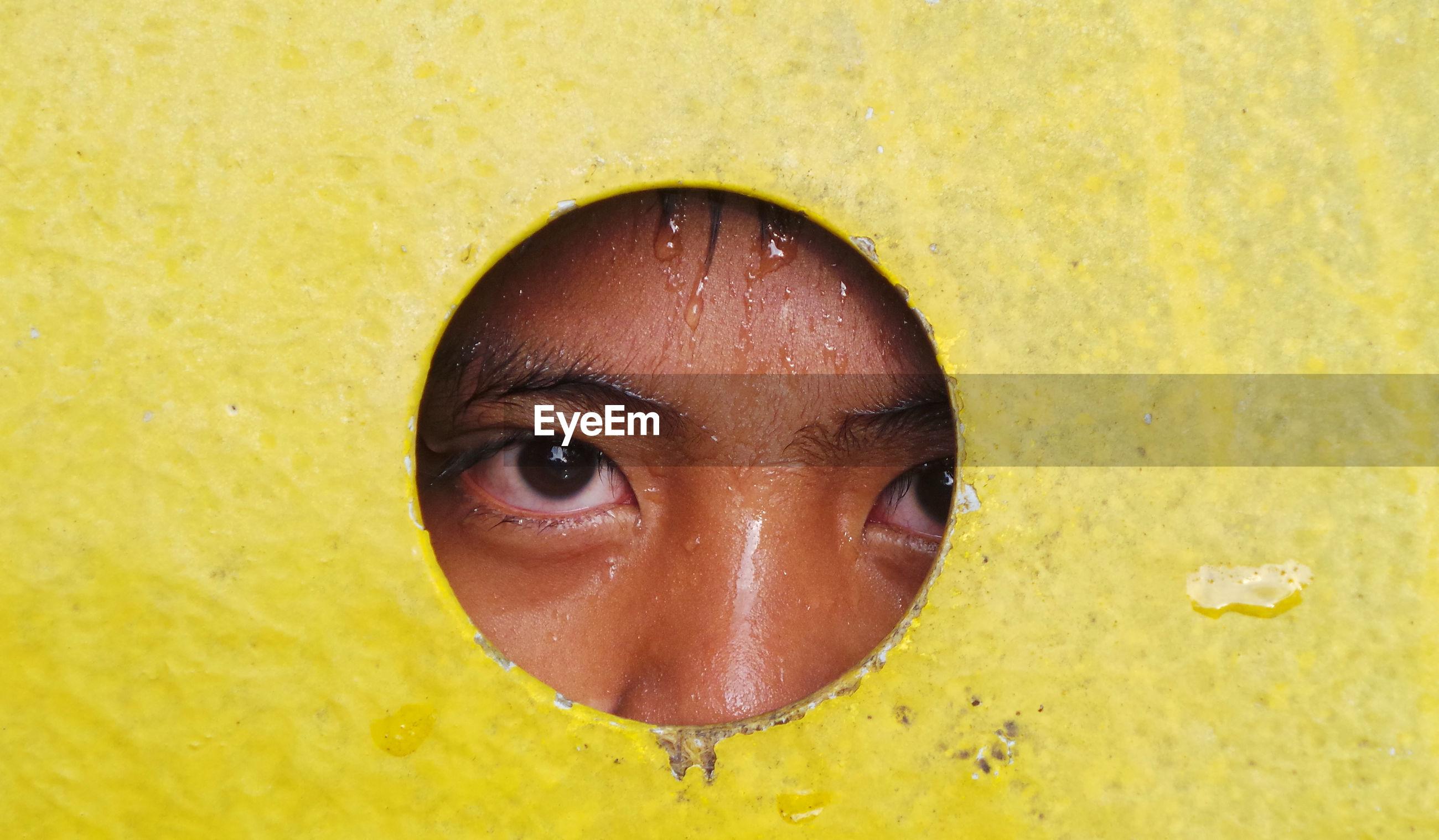 Portrait of wet person peeking through hole
