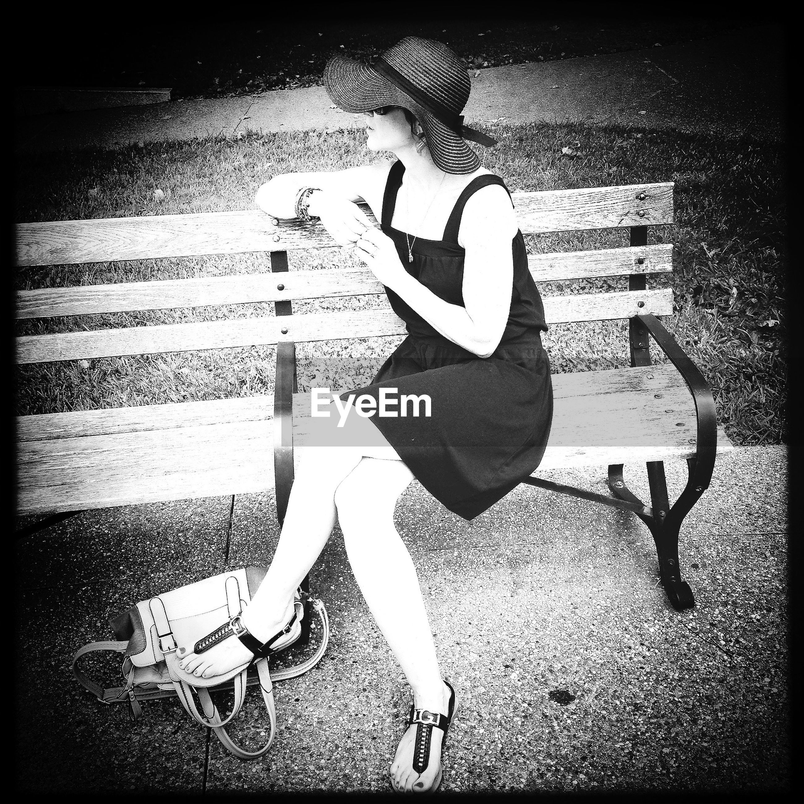 Side view of young woman sitting on park bench
