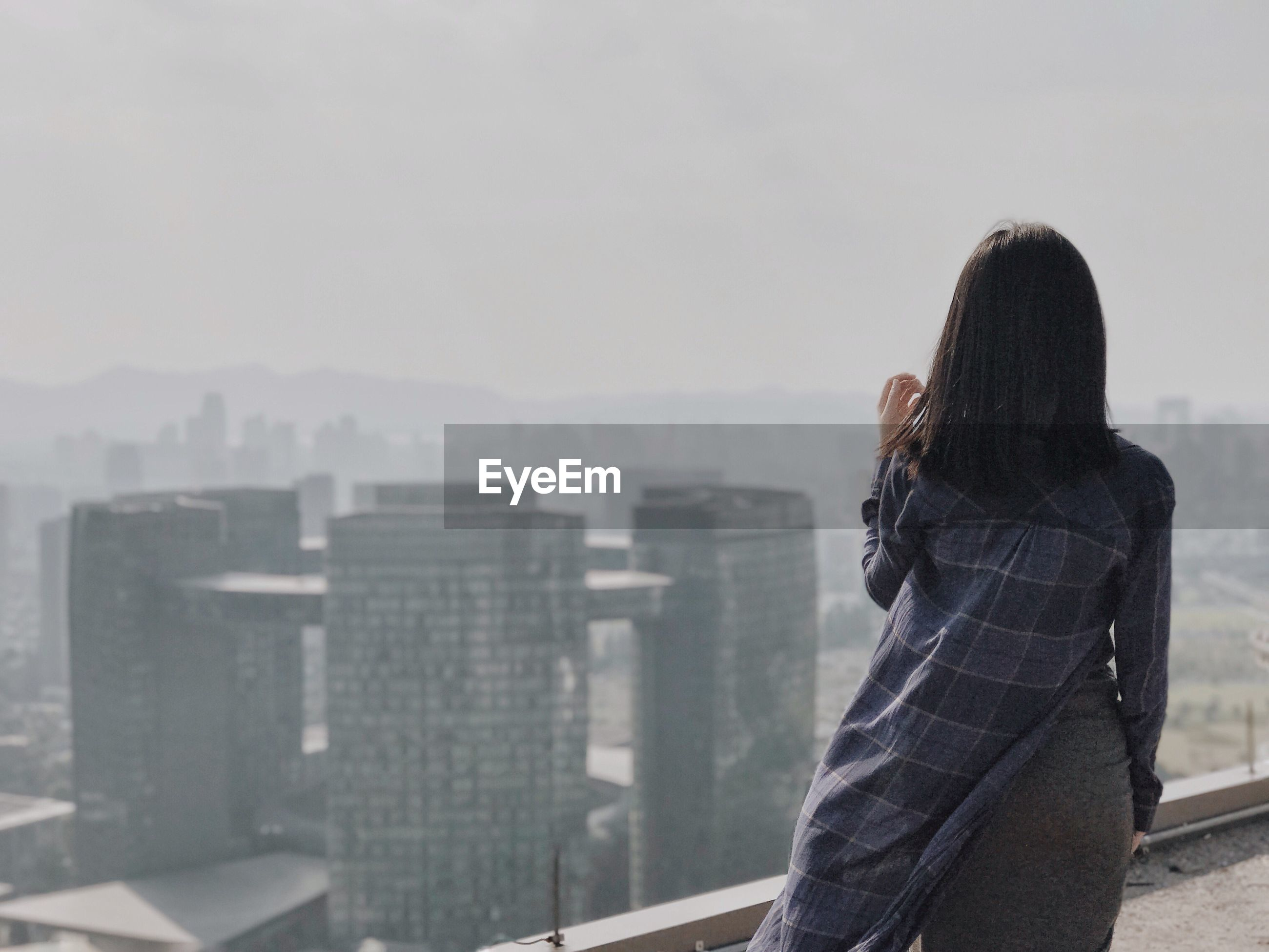 Rear view of young woman on terrace against cityscape