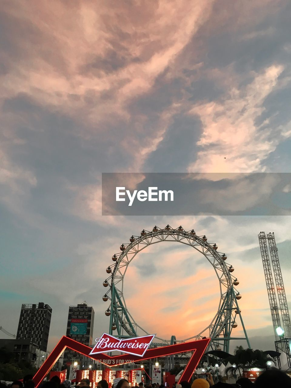 LOW ANGLE VIEW OF FERRIS WHEEL AGAINST SKY IN CITY