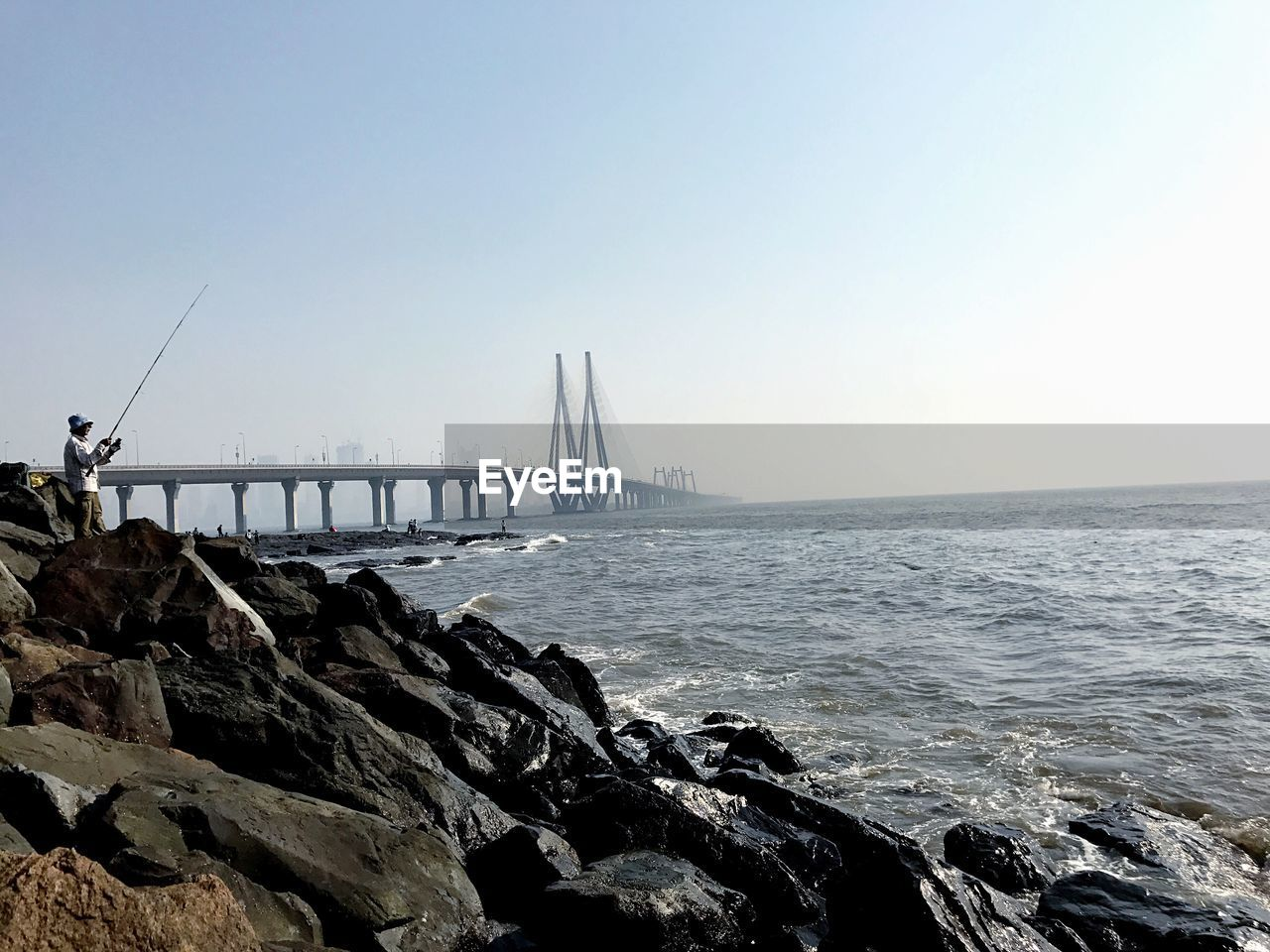 Man fishing at seashore with bandra worli sea link in background