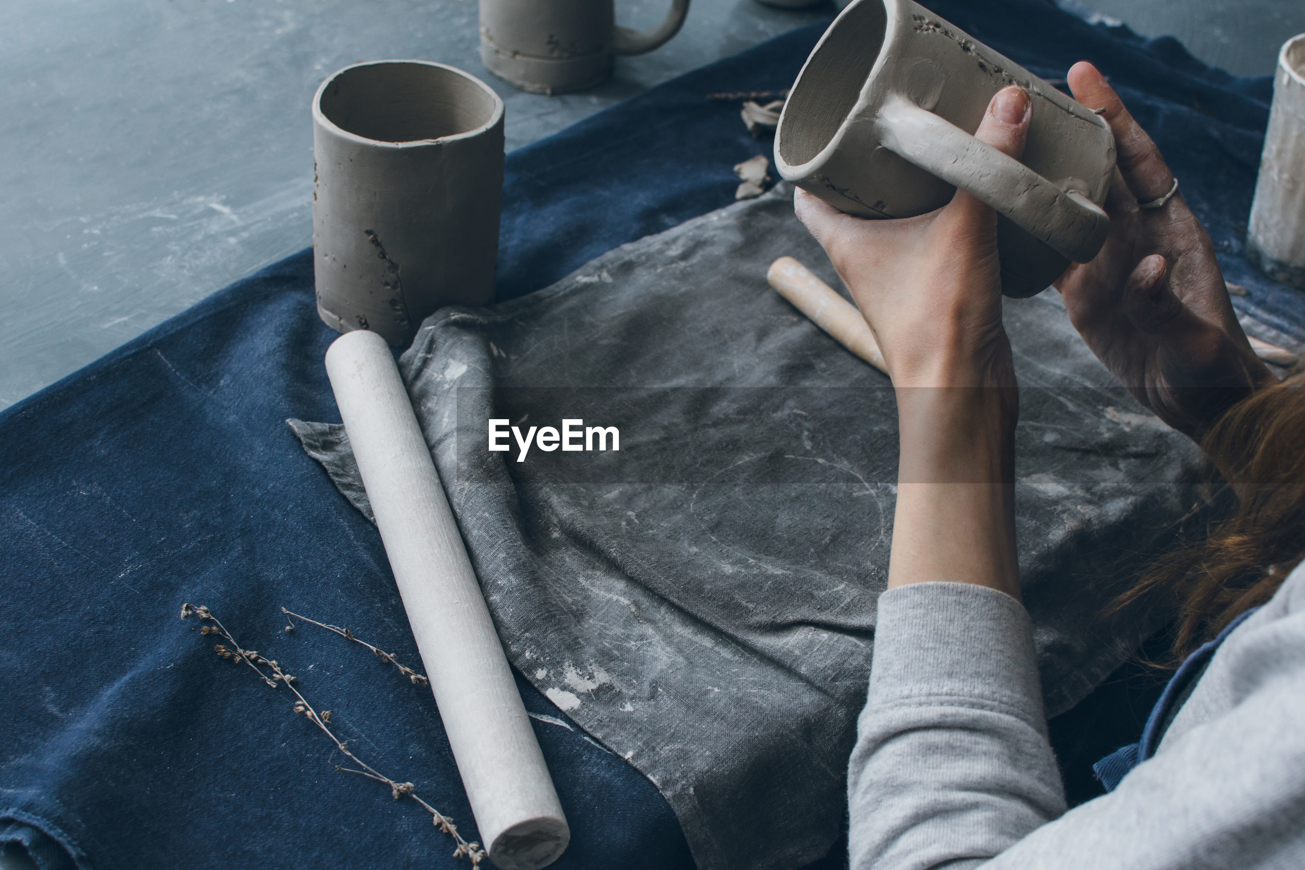 Cropped hands of woman making mug on table