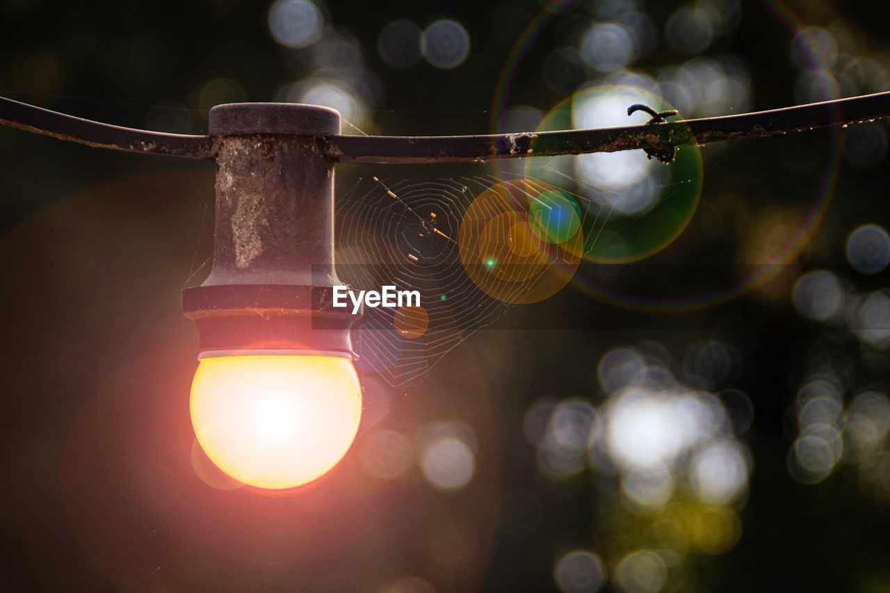 focus on foreground, close-up, lens flare, no people, hanging, illuminated, nature, selective focus, multi colored, outdoors, sunlight, day, shape, lighting equipment, water, glowing, design, rope, light - natural phenomenon, low angle view