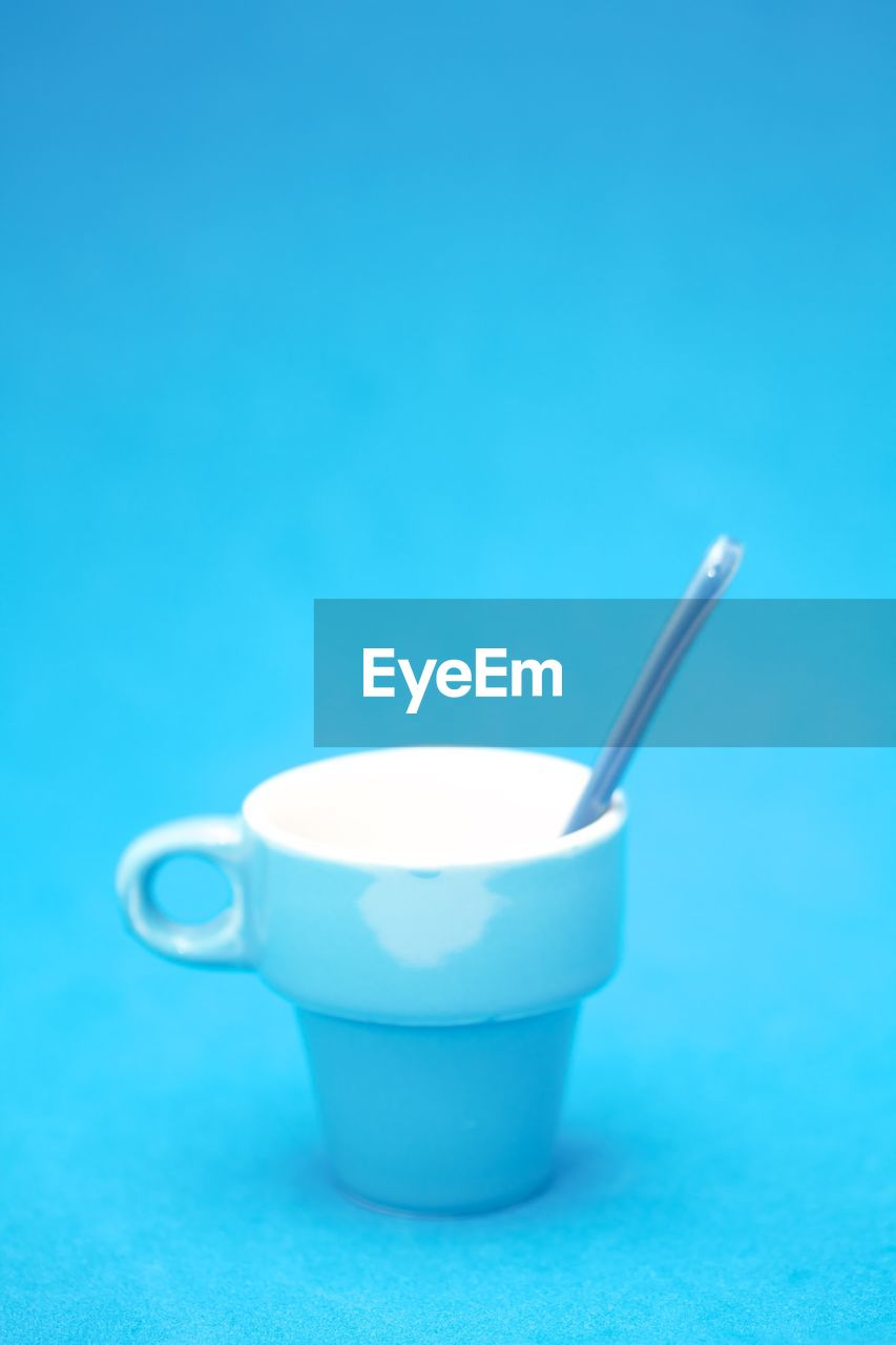Close-up of cup over blue background