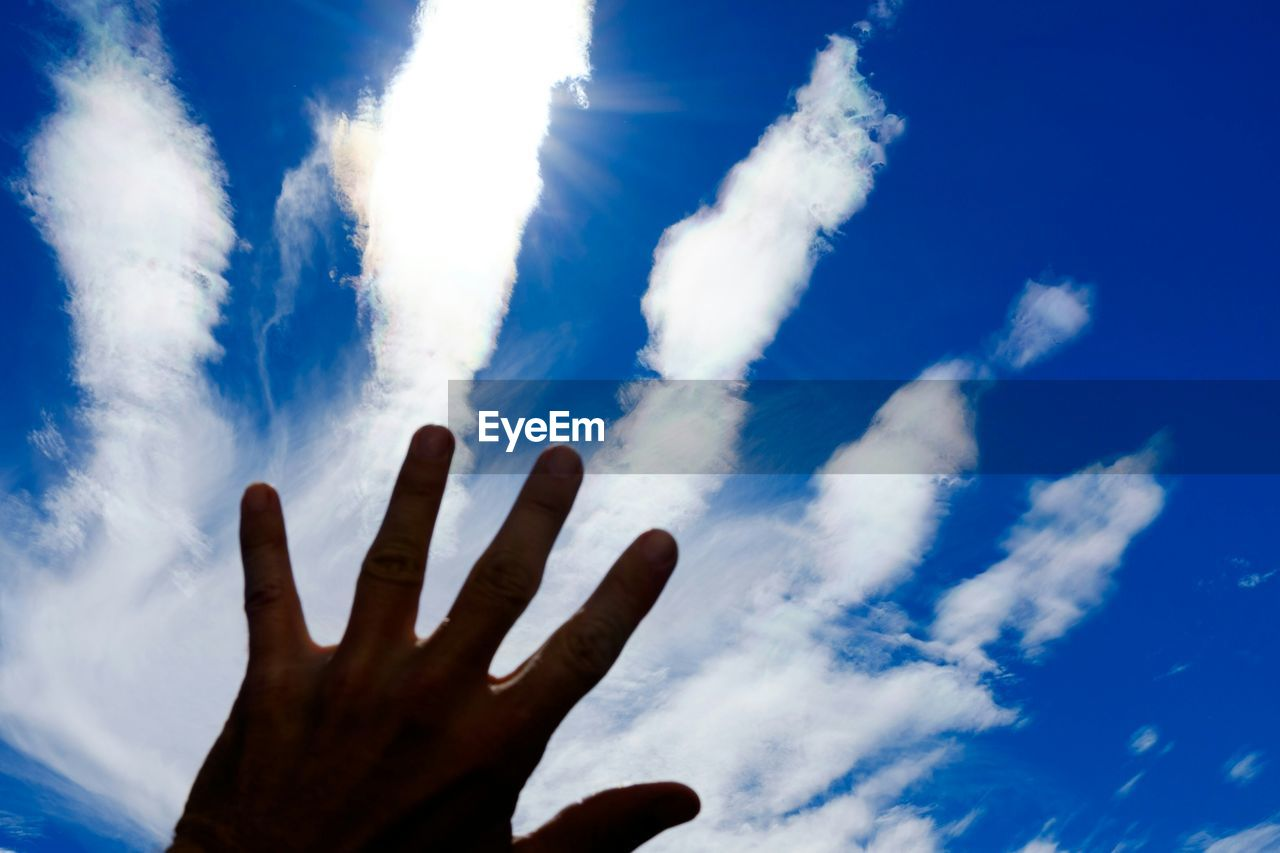 Cropped image of hand against sky