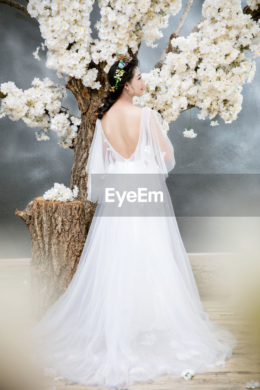 Rear view of bride standing against tree