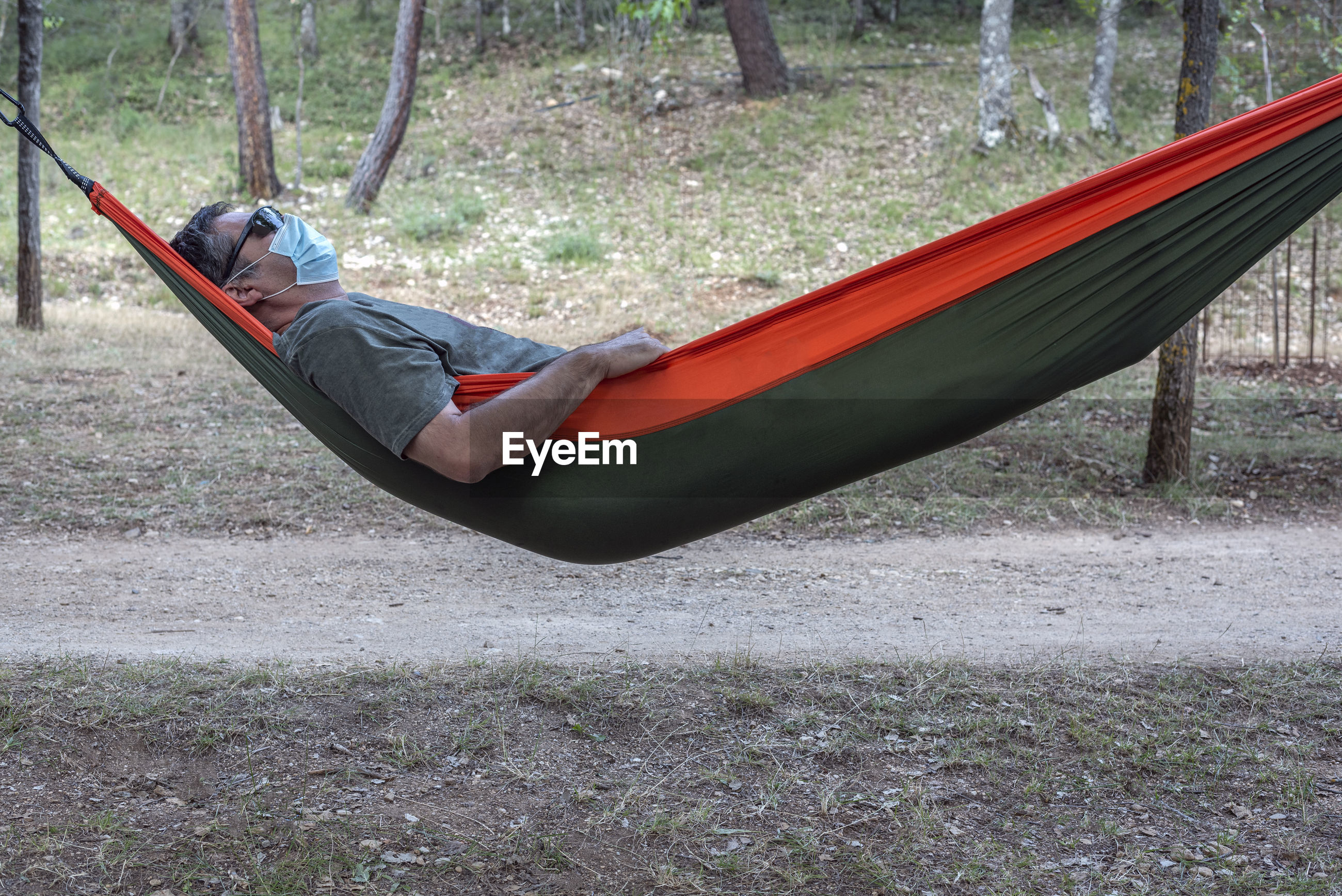Man wearing mask lying on hammock in forest