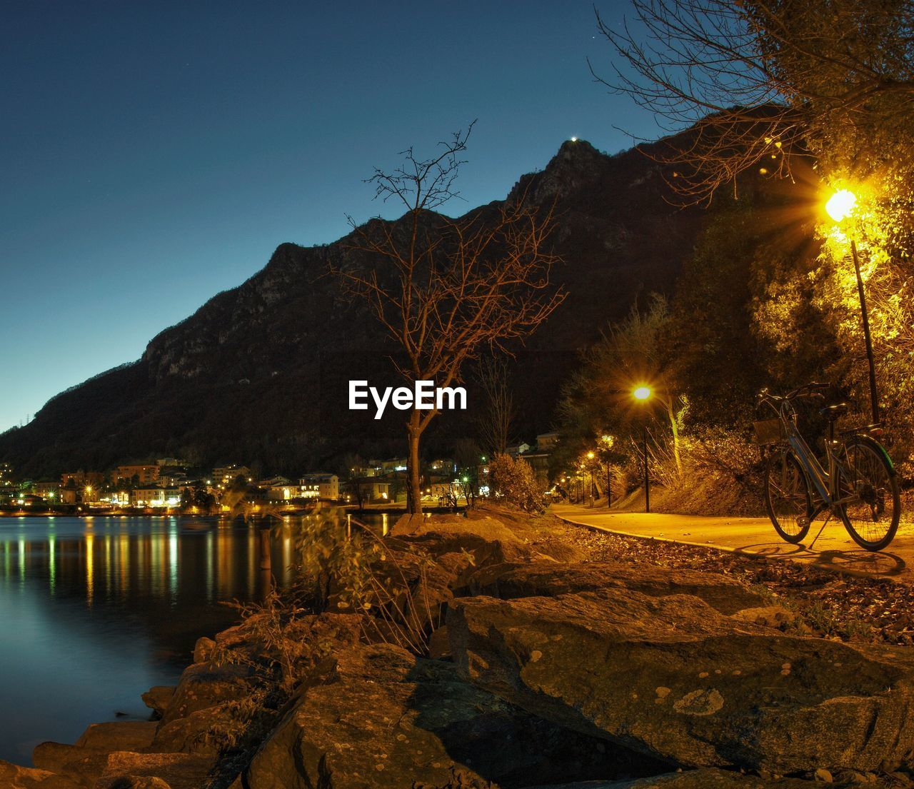 illuminated, water, sky, tree, night, nature, no people, plant, lighting equipment, architecture, street light, street, reflection, built structure, mountain, building exterior, river, outdoors