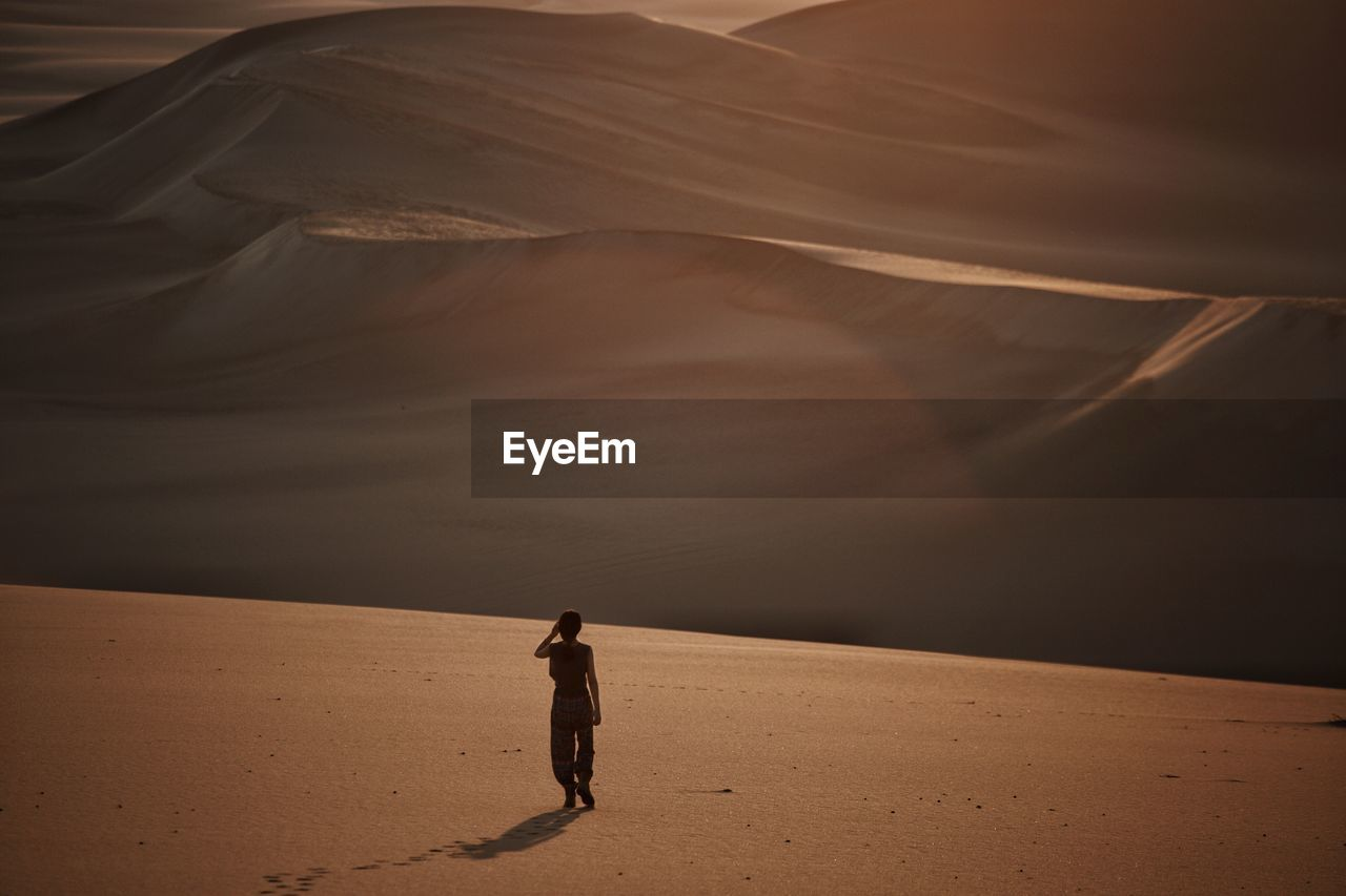 Full Length Of Man Standing On Sand Dune In Desert