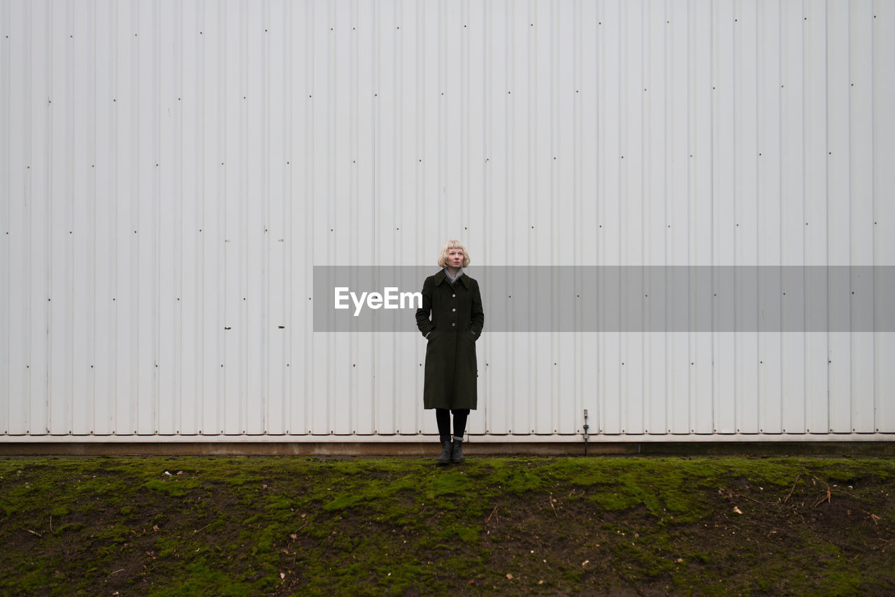 Full Length Of Thoughtful Woman Standing Against White Wall