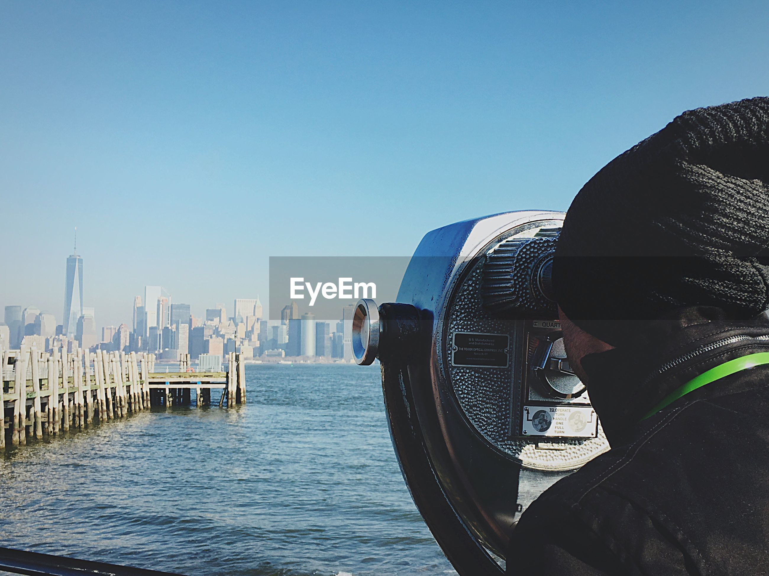 Rear view of man looking at one world trade center through coin-operated binoculars