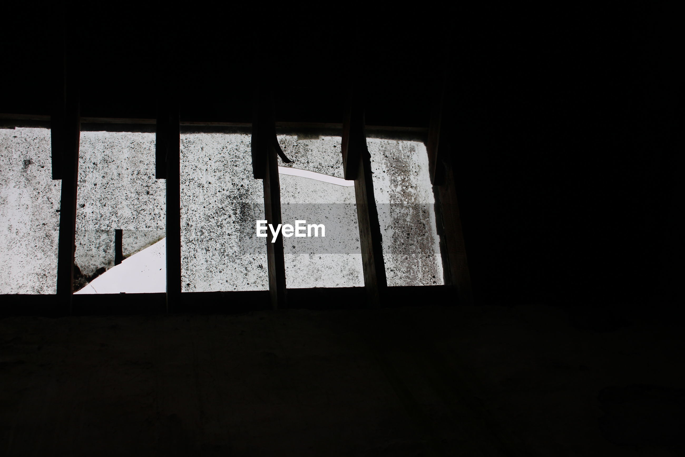 LOW ANGLE VIEW OF SILHOUETTE WINDOW IN ABANDONED BUILDING