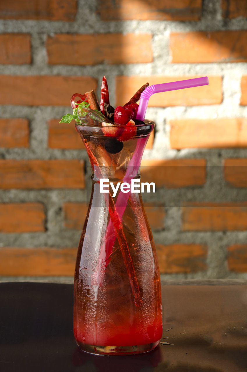 no people, glass - material, indoors, brick wall, still life, close-up, transparent, brick, red, container, wall, table, drink, wall - building feature, focus on foreground, multi colored, glass, food and drink, bottle, mixing