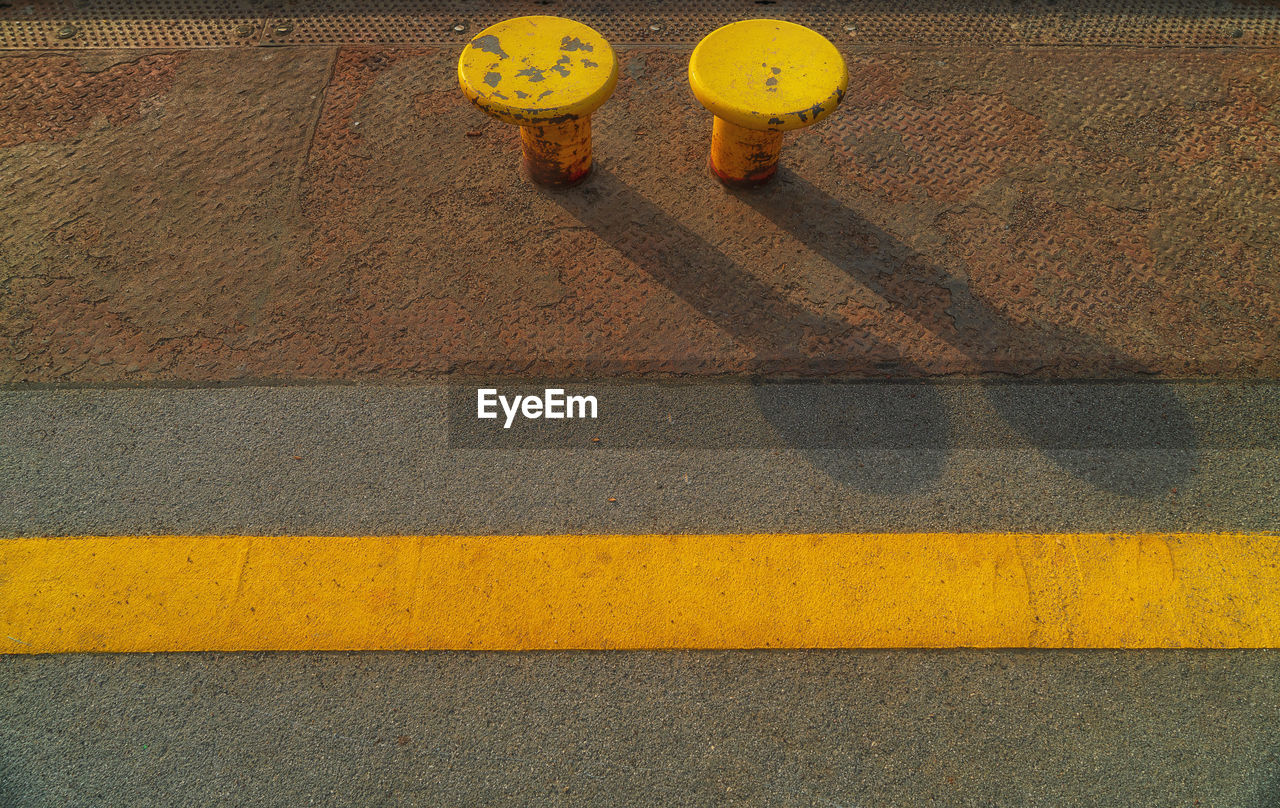 yellow, sign, road, symbol, transportation, road marking, marking, high angle view, city, street, day, protection, crosswalk, safety, guidance, security, striped, outdoors, crossing, zebra crossing, no people