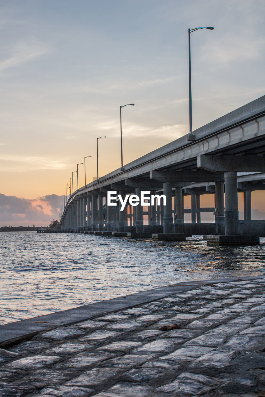 water, sky, built structure, architecture, sunset, bridge, bridge - man made structure, cloud - sky, connection, sea, nature, waterfront, transportation, no people, scenics - nature, motion, pier, architectural column, outdoors, long