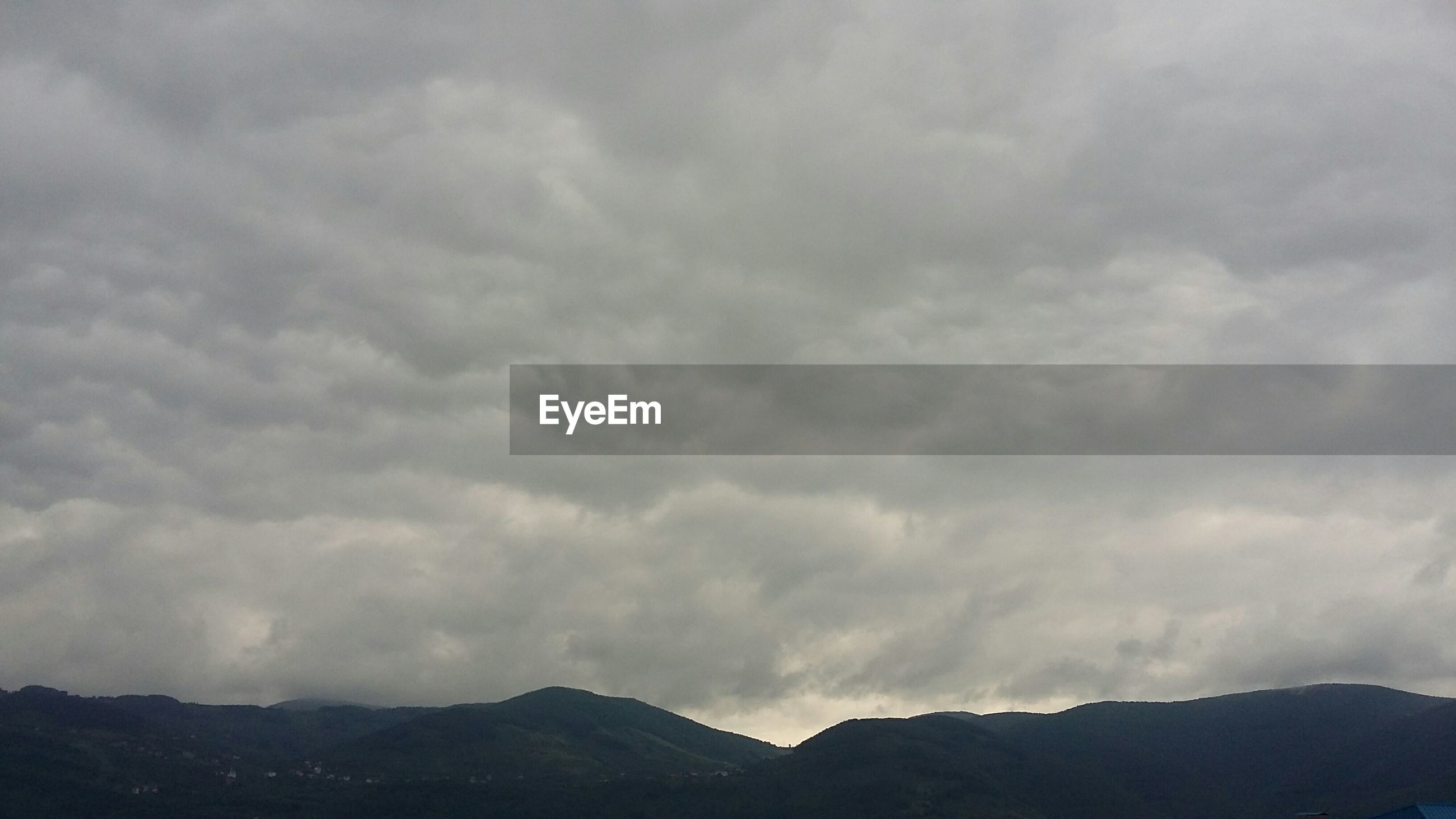 mountain, sky, cloud - sky, scenics, tranquil scene, cloudy, tranquility, beauty in nature, mountain range, nature, weather, cloud, landscape, overcast, idyllic, low angle view, non-urban scene, outdoors, cloudscape, day