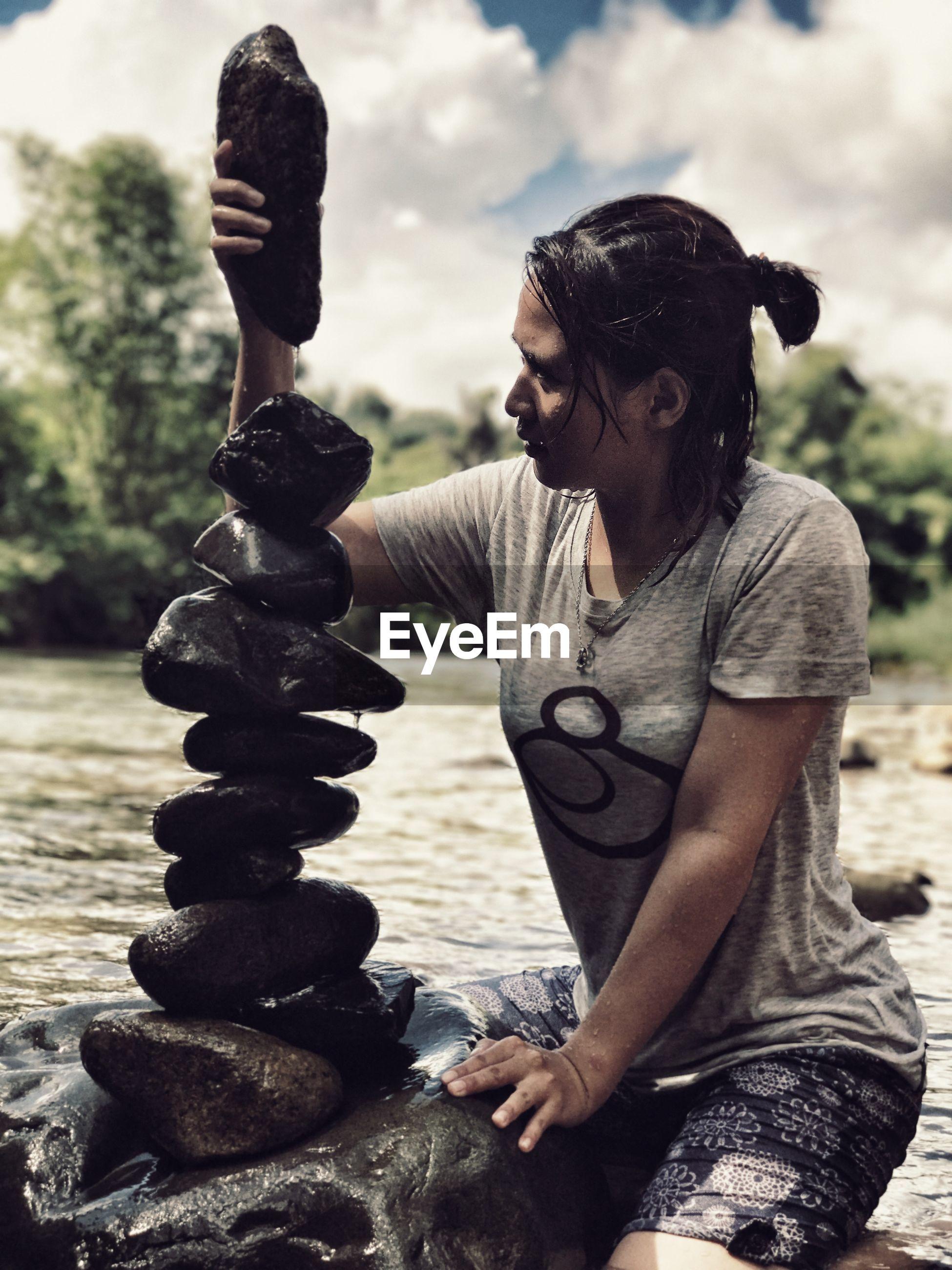 Young woman stacking stones at riverbank