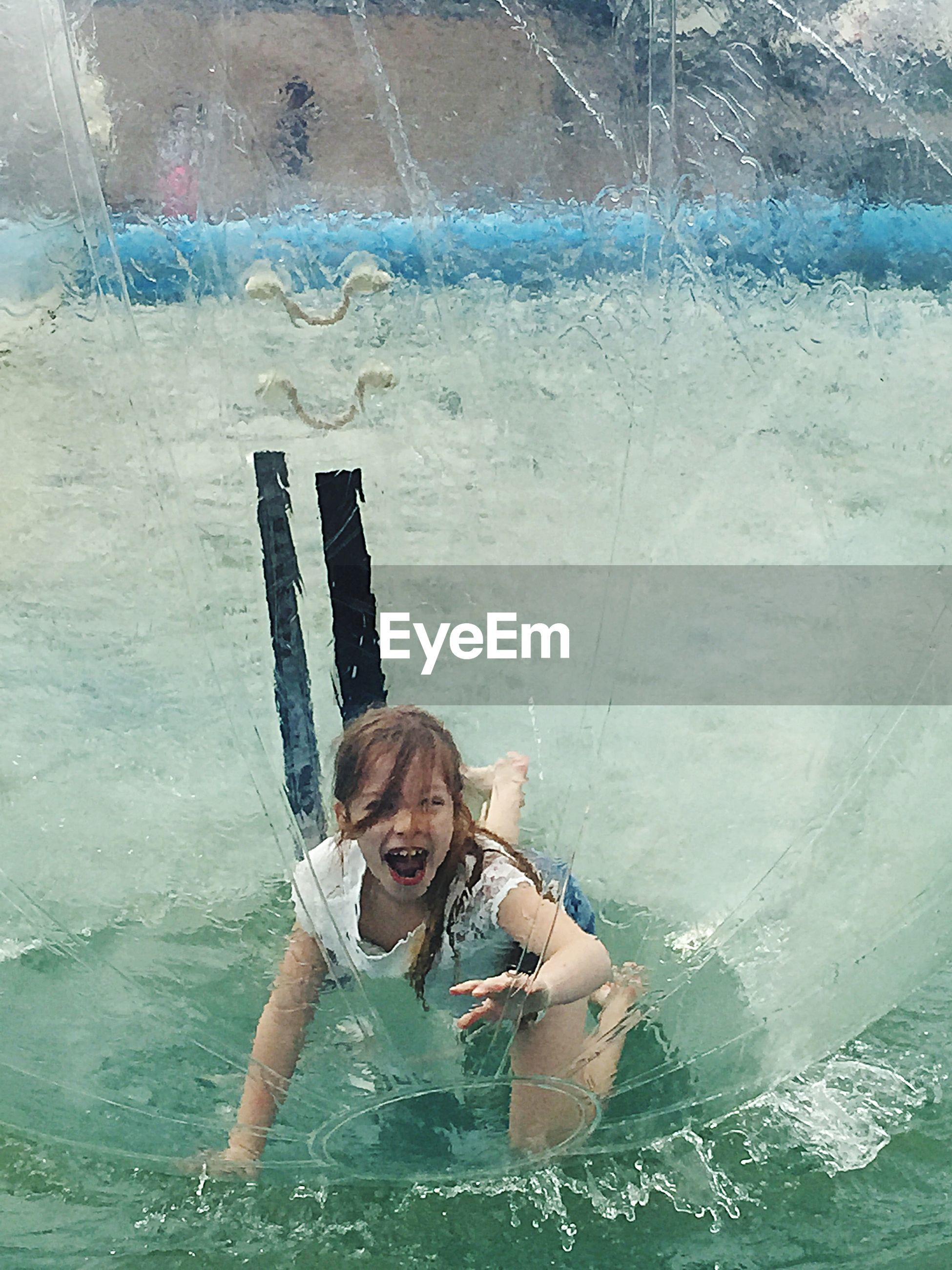 Girl playing in inflated ball over pool