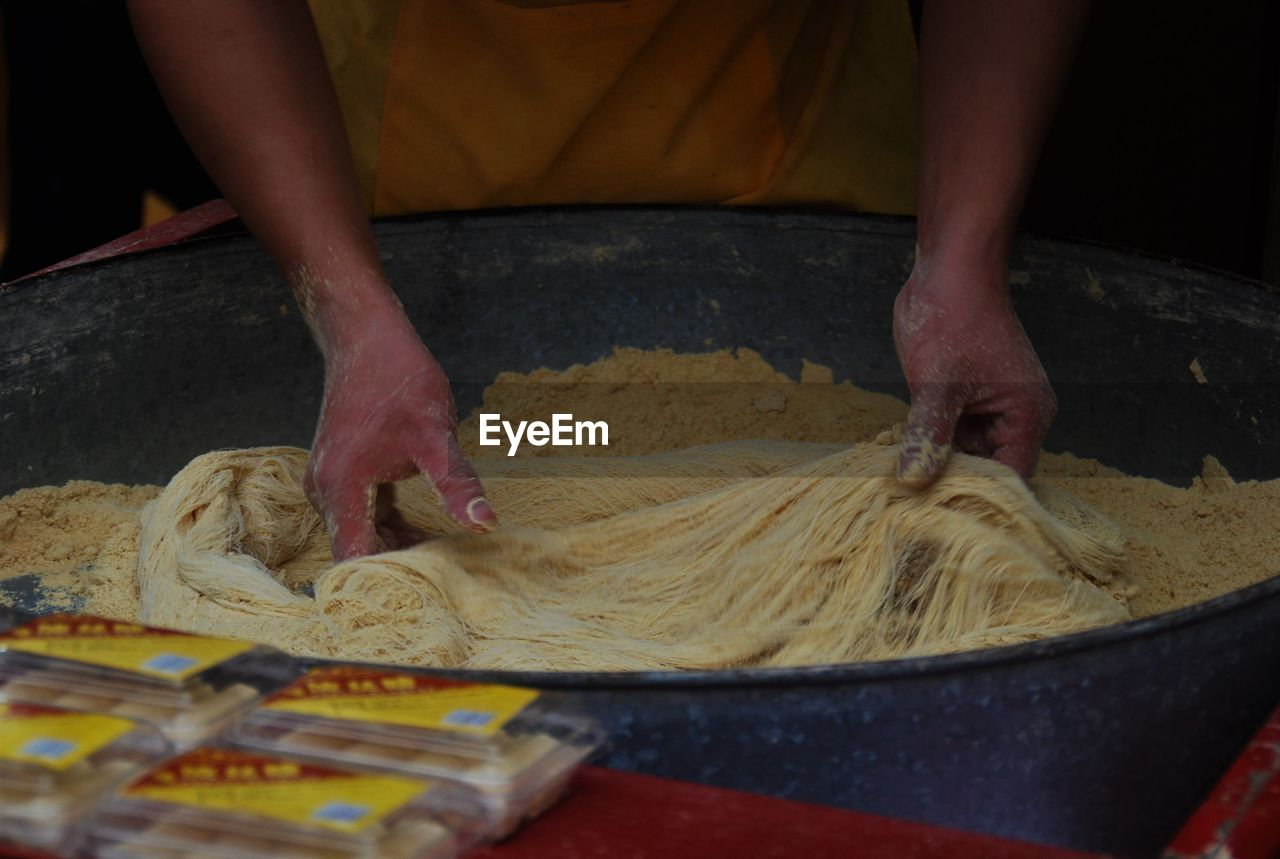 Midsection Of Chef Preparing Noodles At Street Market Stall