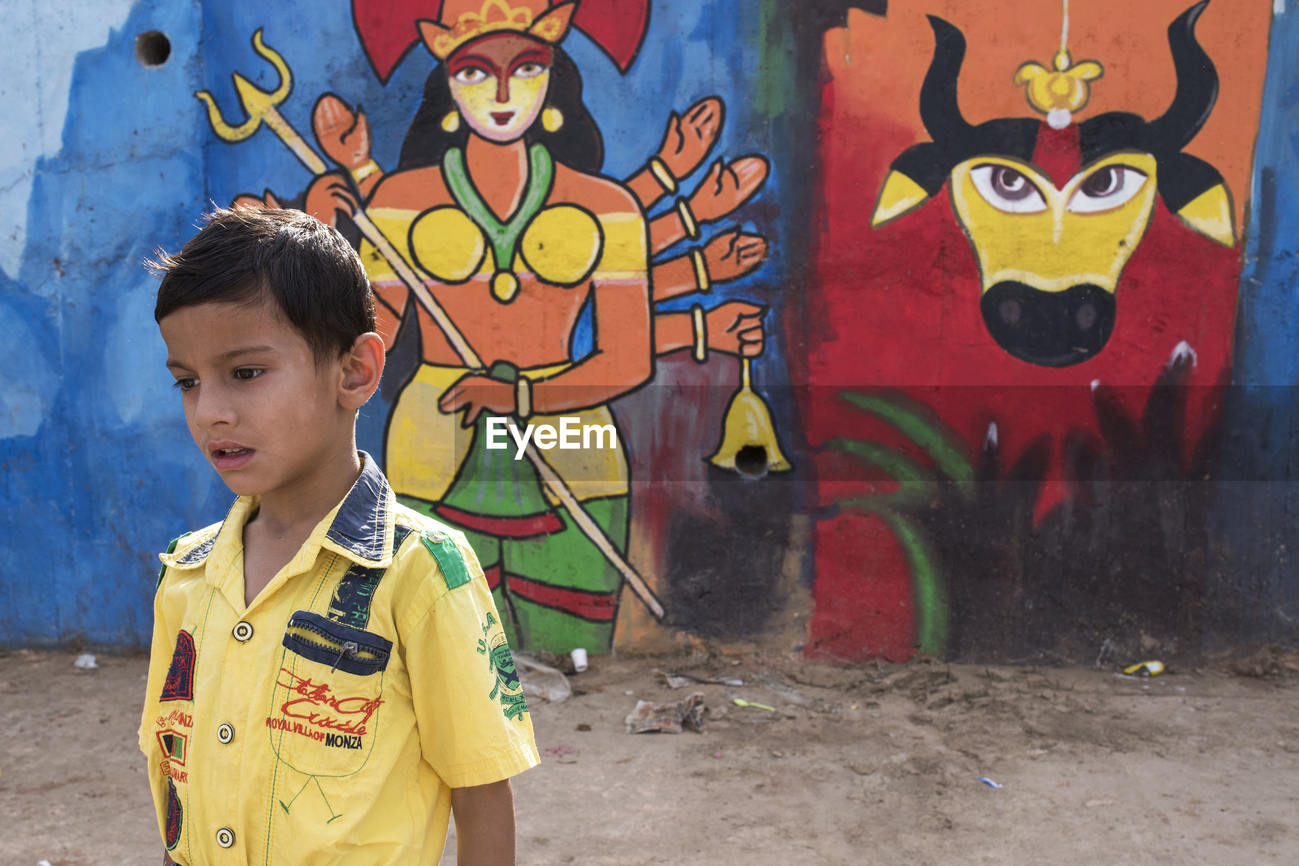 FULL LENGTH OF BOY STANDING IN MULTI COLORED GRAFFITI