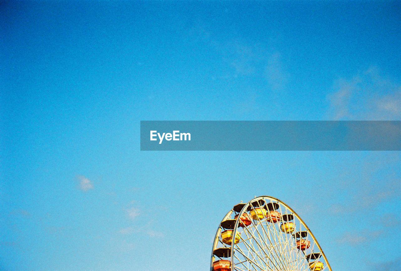 amusement park, arts culture and entertainment, low angle view, ferris wheel, blue, amusement park ride, no people, sky, day, outdoors, big wheel