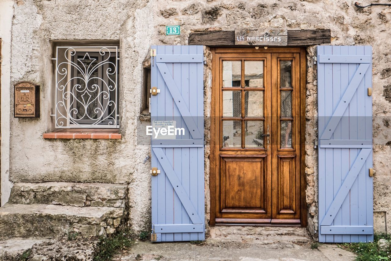 built structure, architecture, building exterior, door, entrance, no people, building, day, closed, house, wall - building feature, security, wood - material, safety, protection, outdoors, old, wall, window, residential district, stone wall