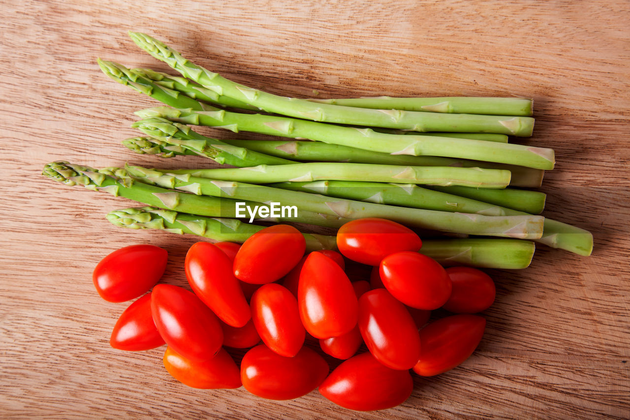 vegetable, food and drink, food, freshness, wellbeing, still life, healthy eating, green color, indoors, raw food, table, wood - material, directly above, no people, close-up, large group of objects, high angle view, asparagus, pepper, red, vegetarian food, chopped