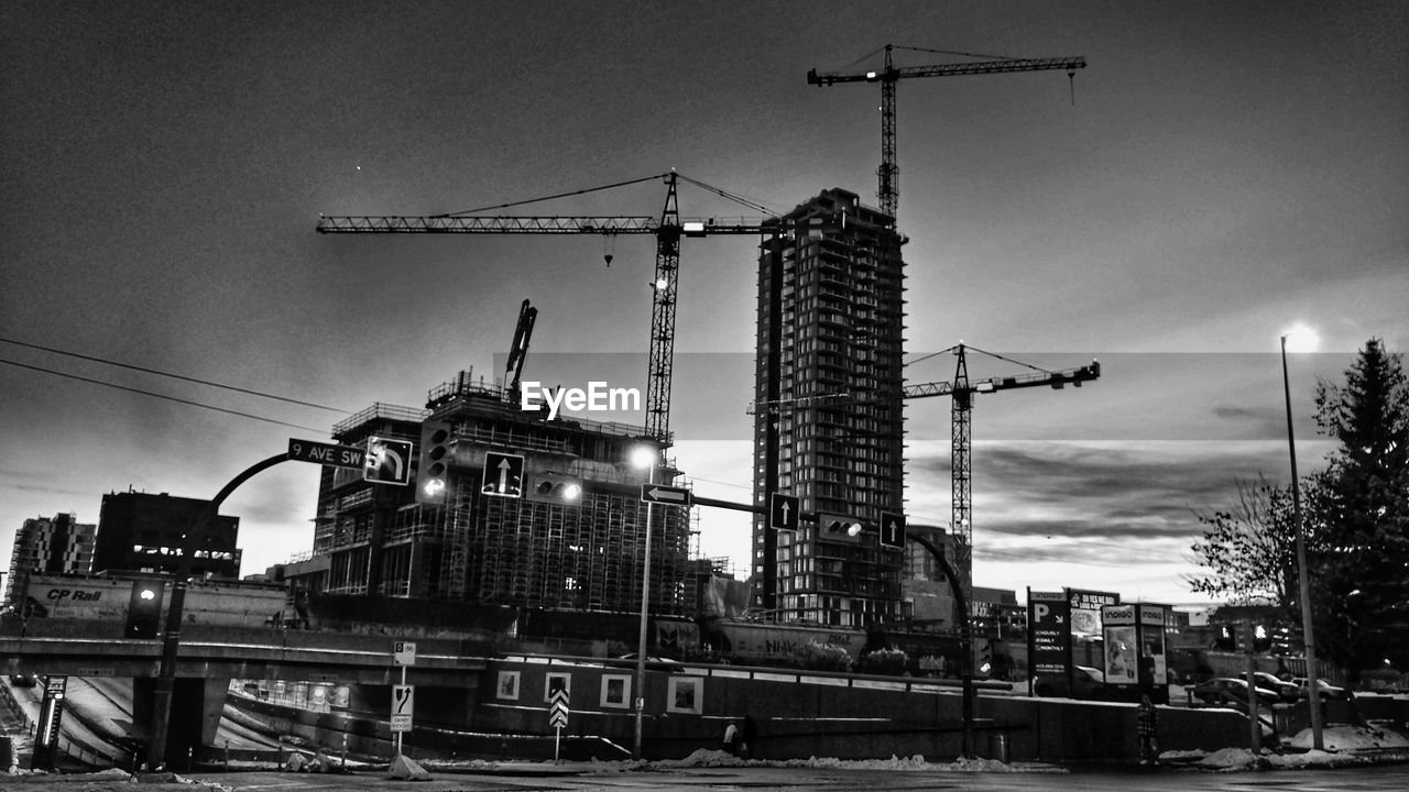 architecture, construction site, built structure, development, building exterior, crane - construction machinery, sky, low angle view, crane, industry, construction, outdoors, city, no people, progress, day, illuminated