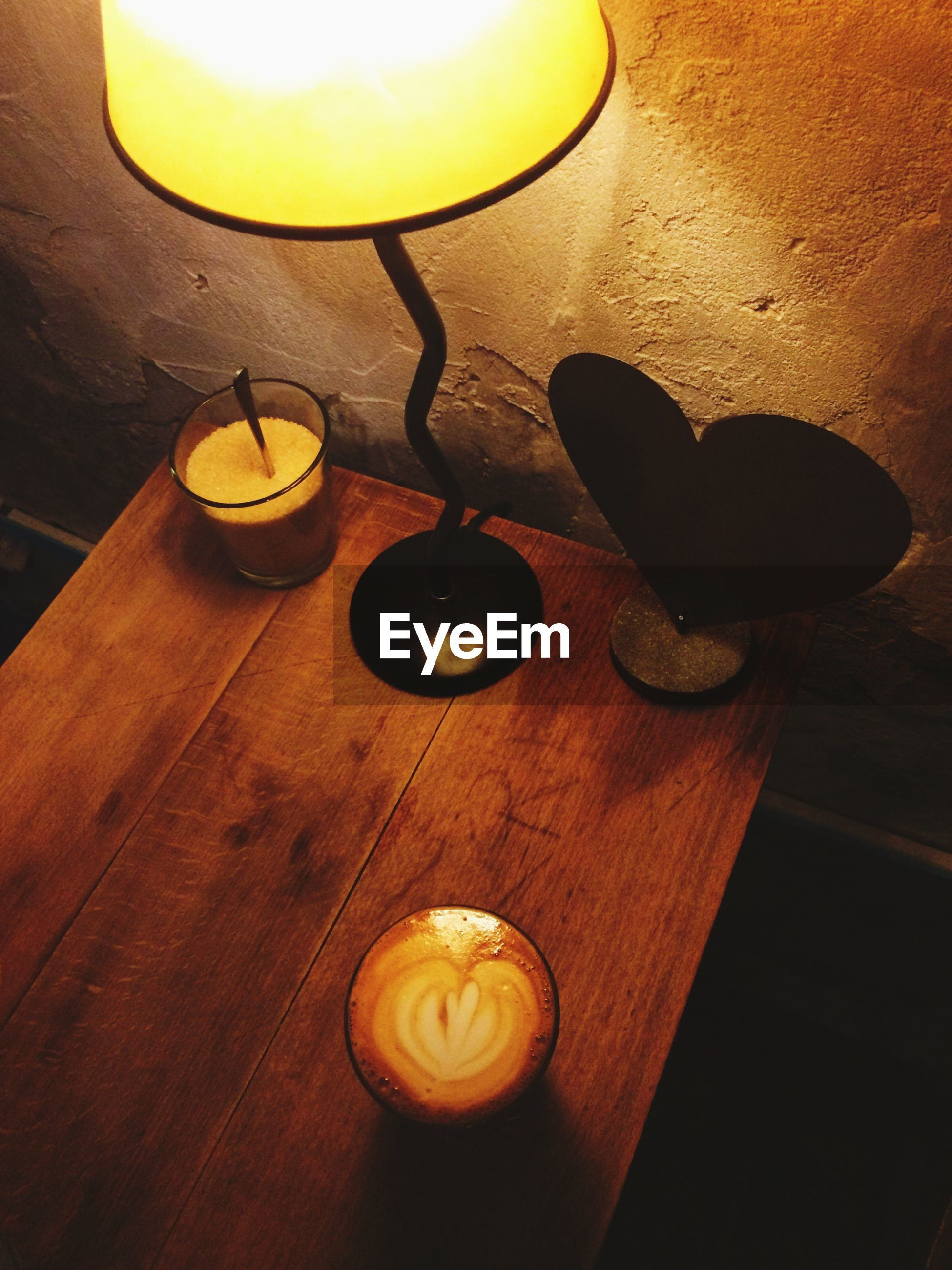 High angle view of illuminated electric lamp with coffee on wooden table