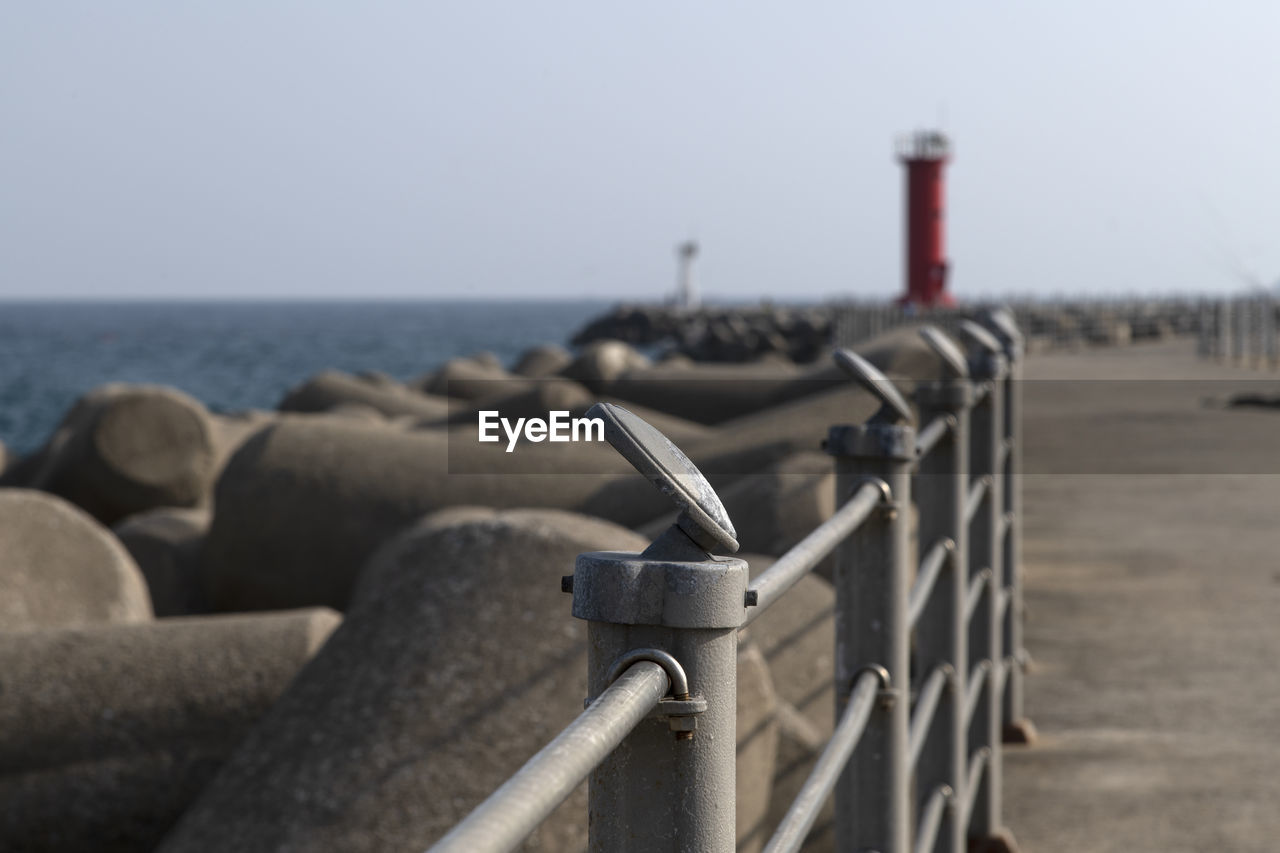 sky, sea, security, water, protection, horizon over water, nature, focus on foreground, horizon, beach, metal, safety, day, clear sky, no people, land, railing, outdoors, built structure, concrete