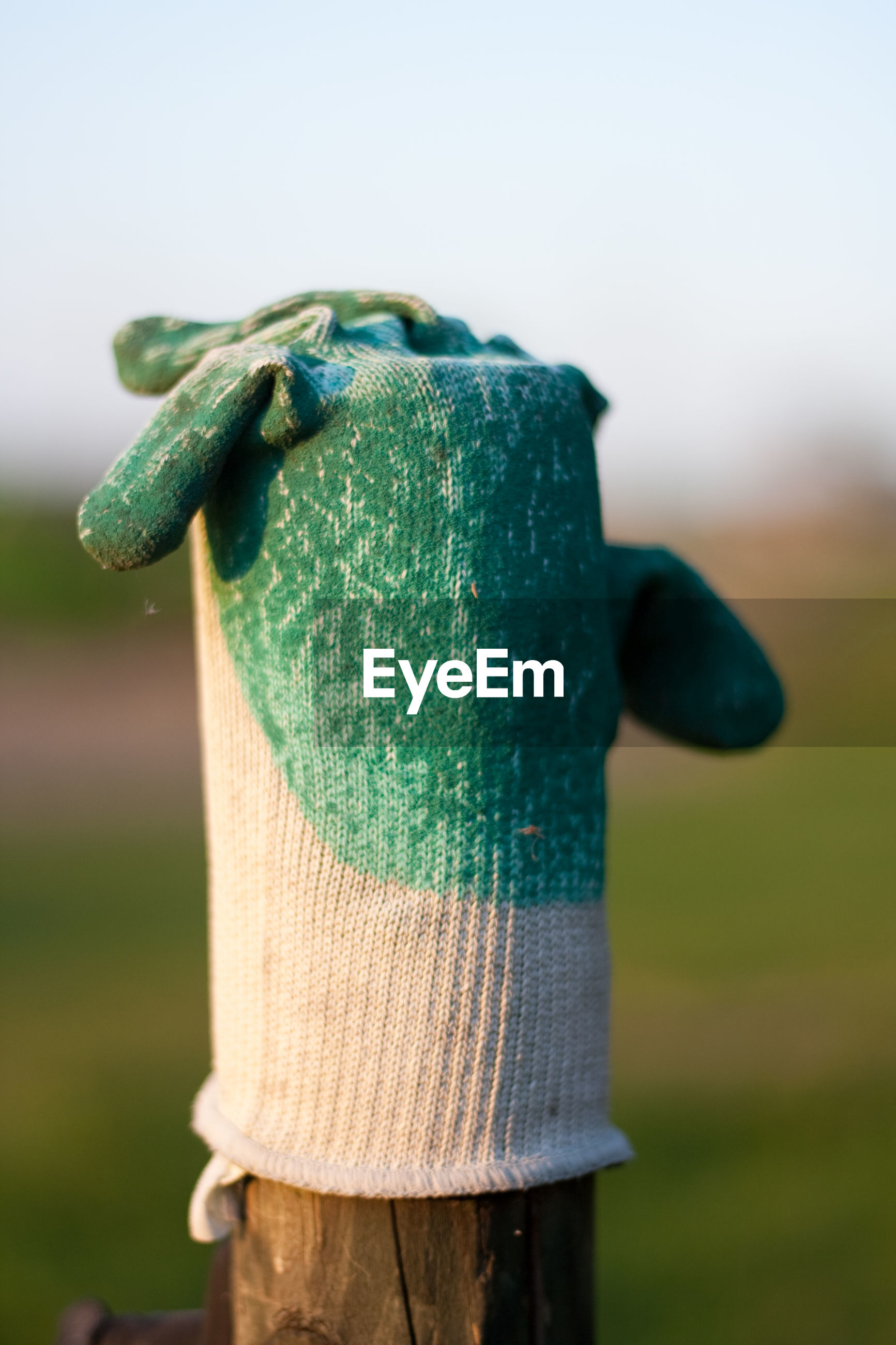 Close-up of gardening glove on wooden post