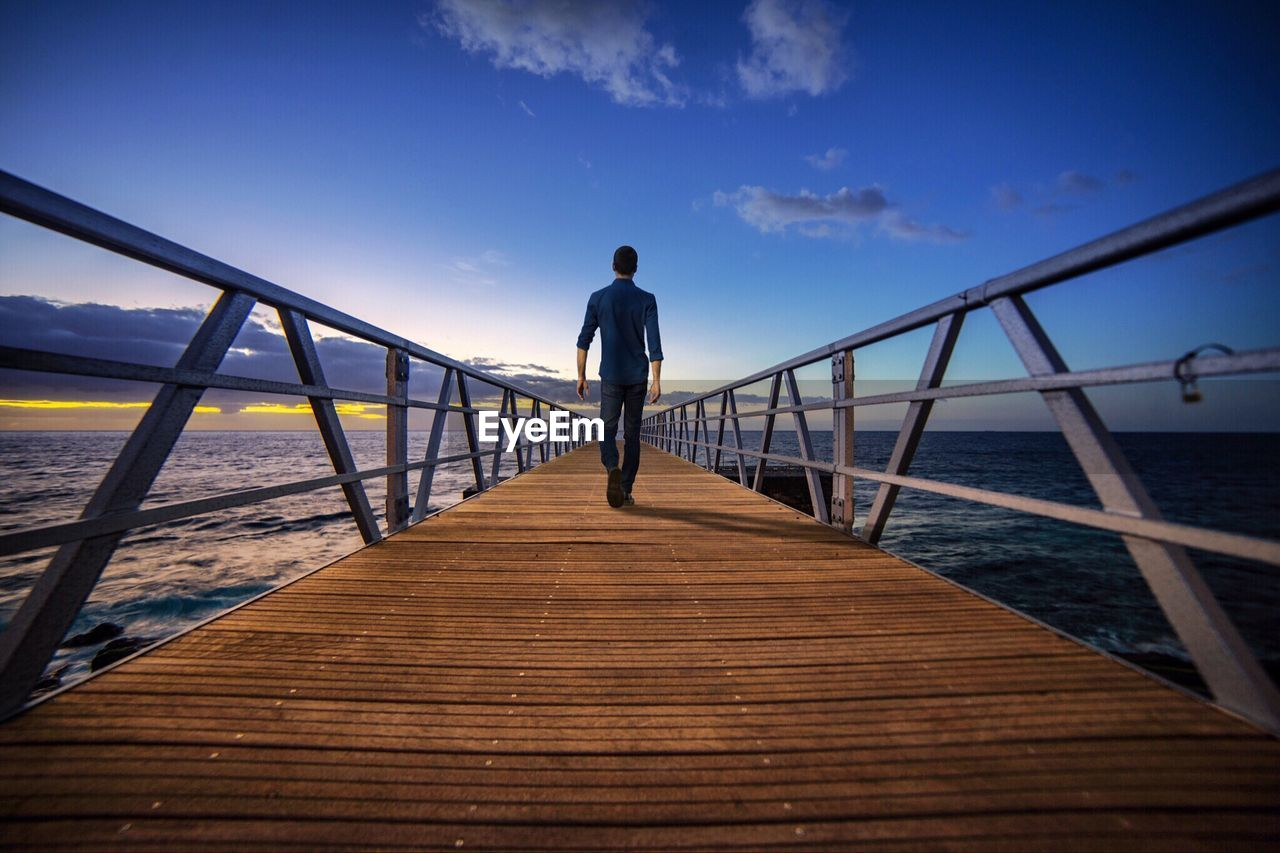 Rear view of mature man walking on pier over sea against sky during sunset