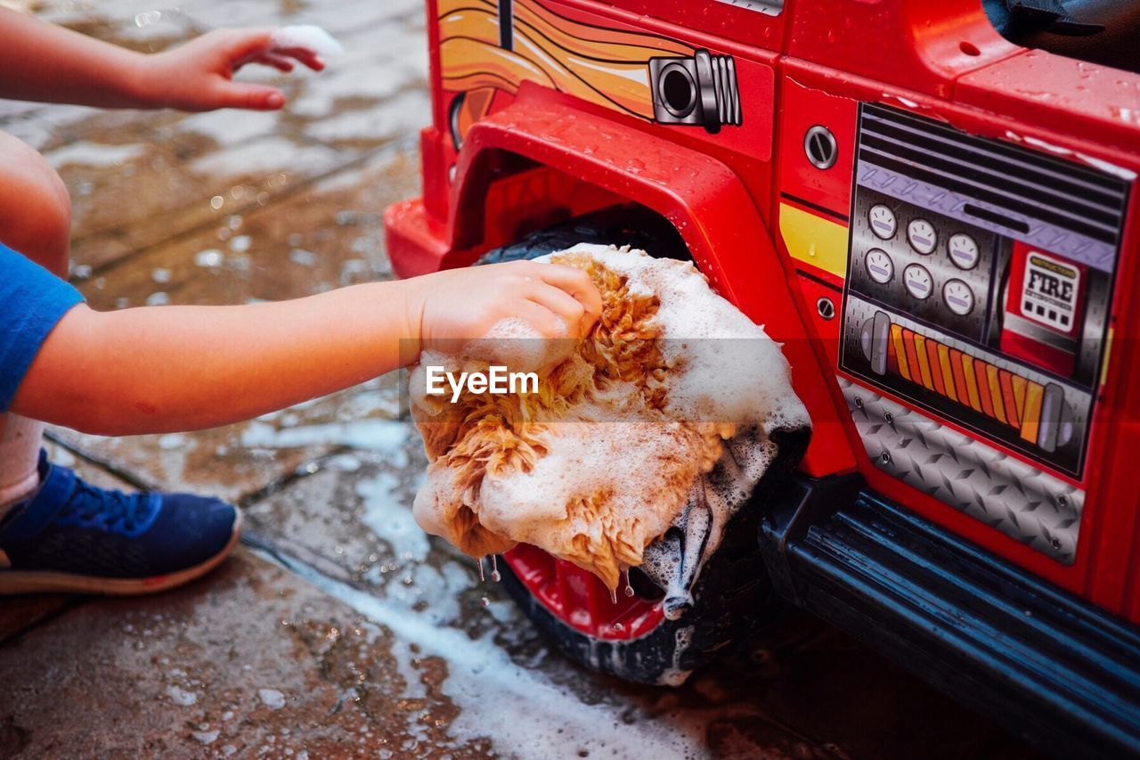 HAND OF BOY WASHING TOY OUTDOORS