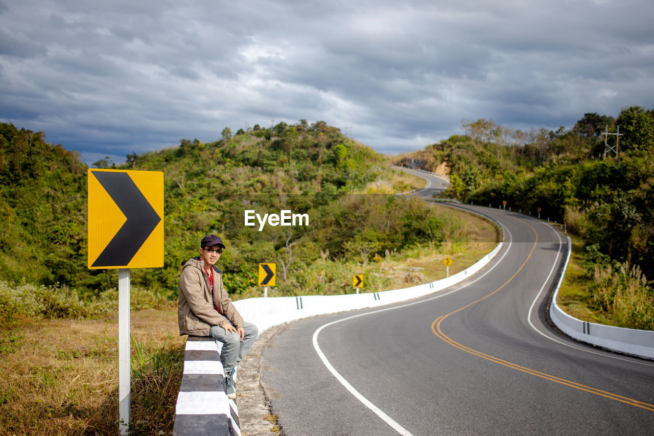 sign, road, transportation, communication, cloud - sky, symbol, direction, tree, one person, plant, road sign, nature, real people, full length, sky, the way forward, lifestyles, guidance, day, road marking, outdoors