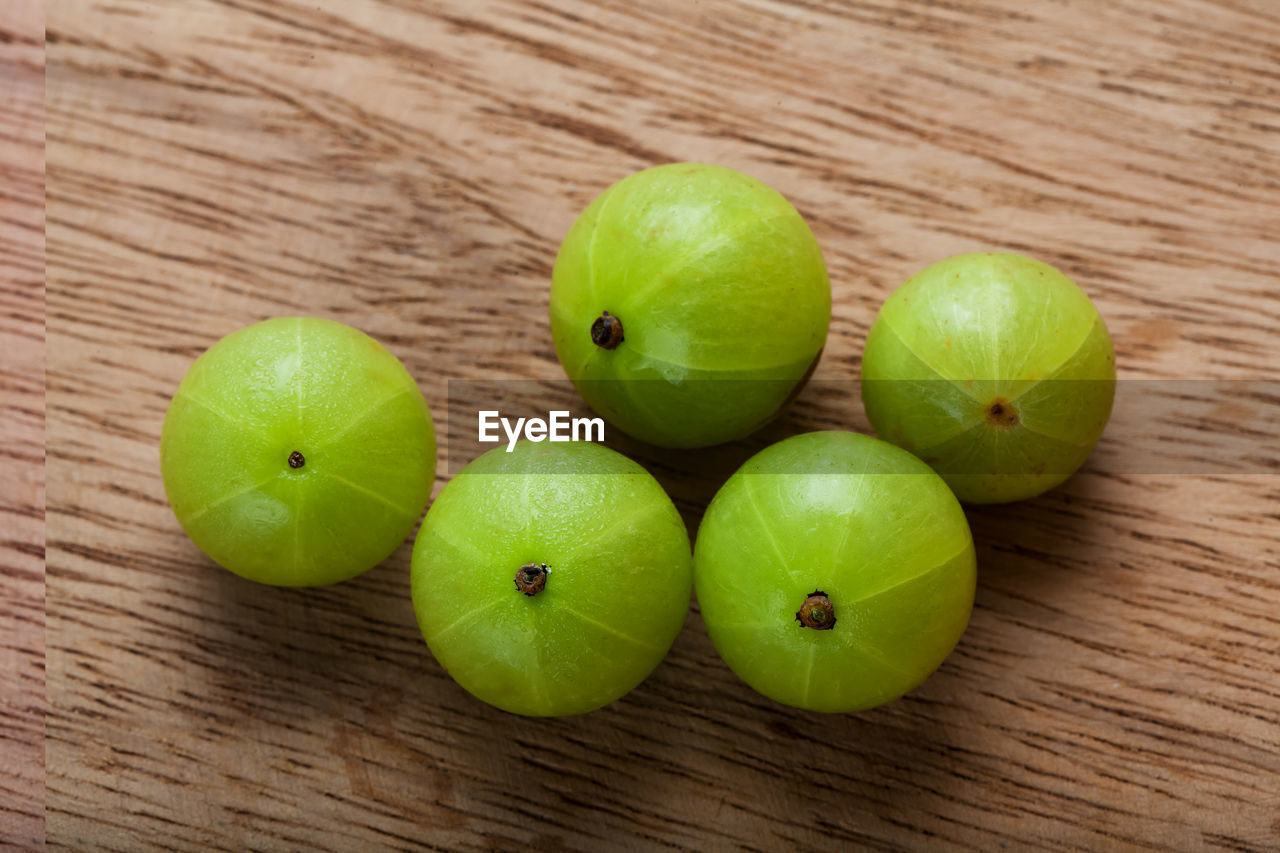 healthy eating, fruit, wellbeing, wood - material, food, table, green color, food and drink, freshness, still life, close-up, high angle view, indoors, no people, group of objects, apple - fruit, granny smith apple, focus on foreground, apple, slice, ripe, wood grain