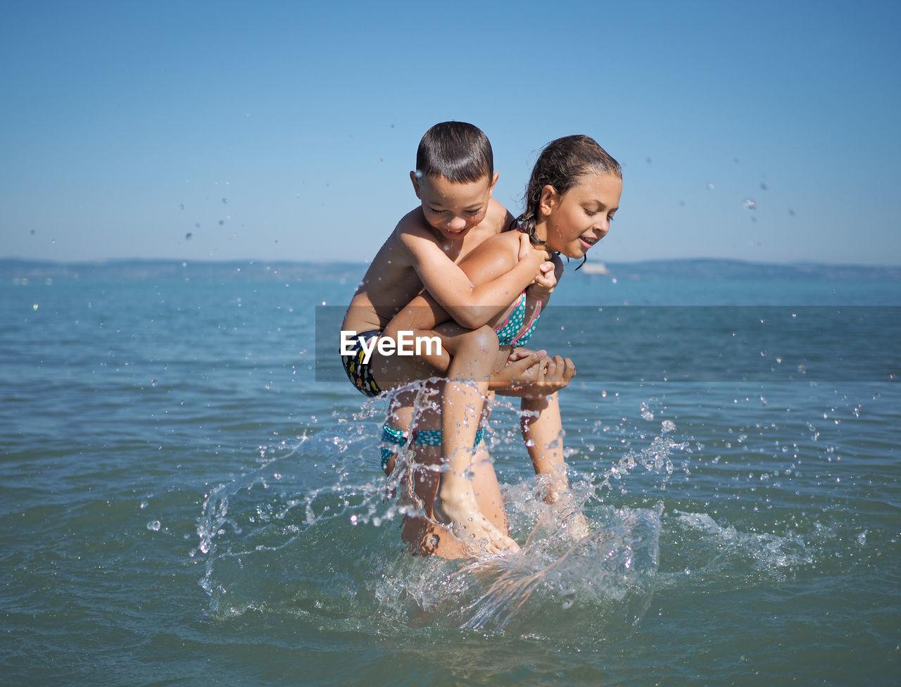 Siblings Wading In Sea Against Clear Sky