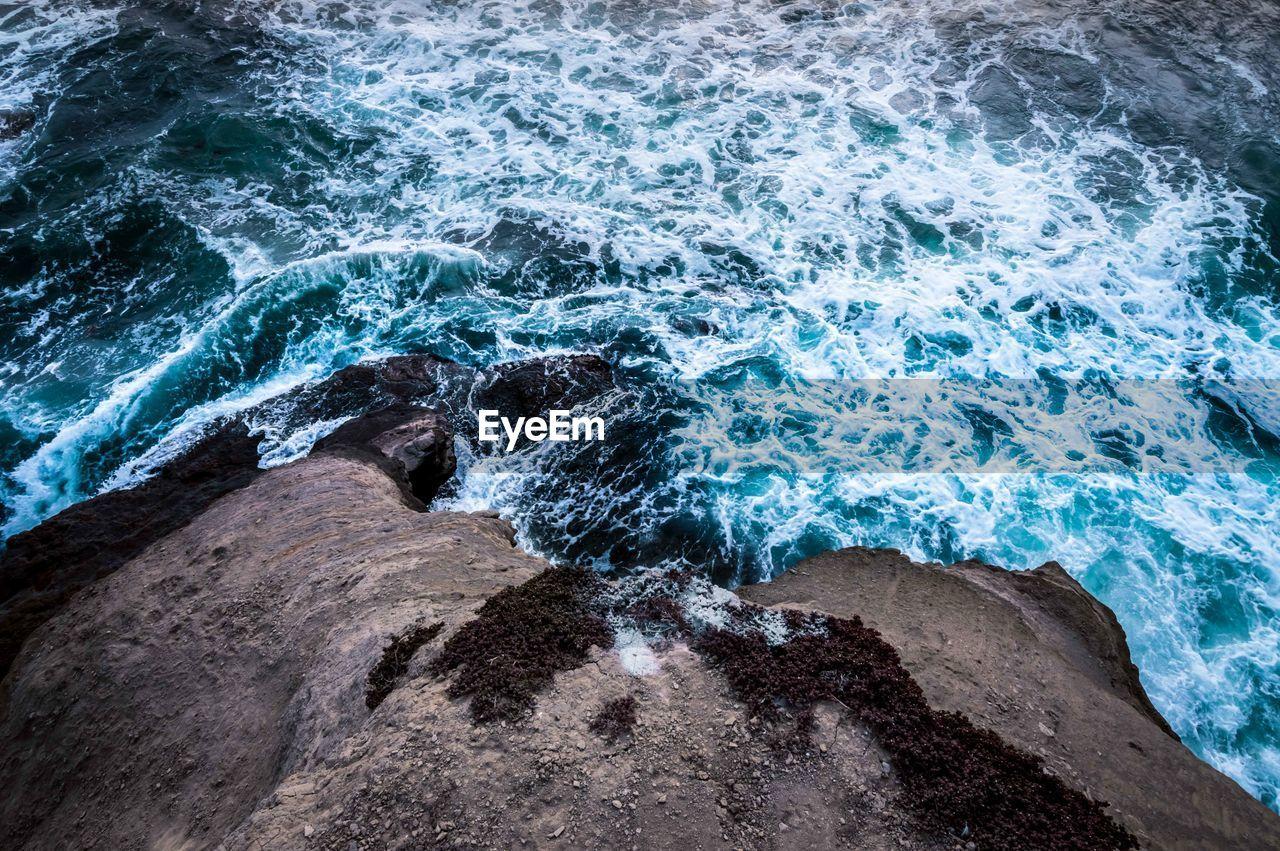 HIGH ANGLE VIEW OF WAVES SPLASHING ON ROCKS AT SHORE