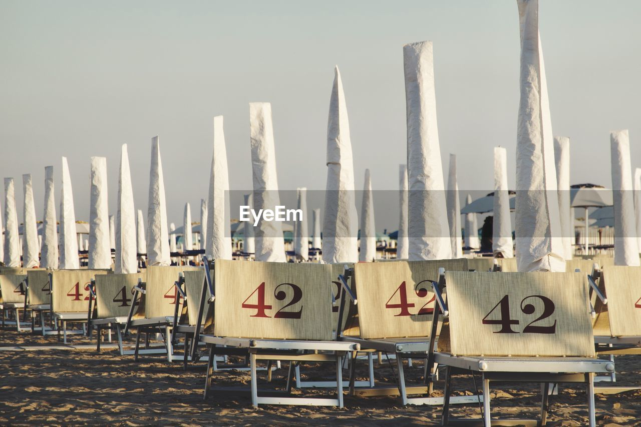 HOODED CHAIRS AT BEACH AGAINST CLEAR SKY