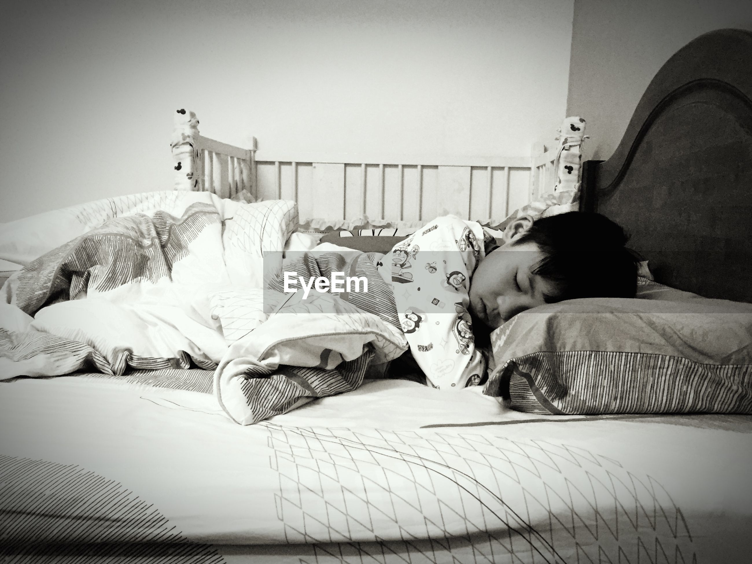 Side view of boy sleeping on bed at home