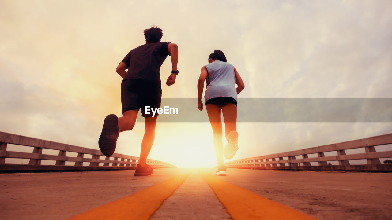 sky, sunset, lifestyles, rear view, nature, full length, leisure activity, two people, cloud - sky, real people, men, women, beauty in nature, adult, sunlight, architecture, people, built structure, orange color, bridge, outdoors, sun, couple - relationship, shorts