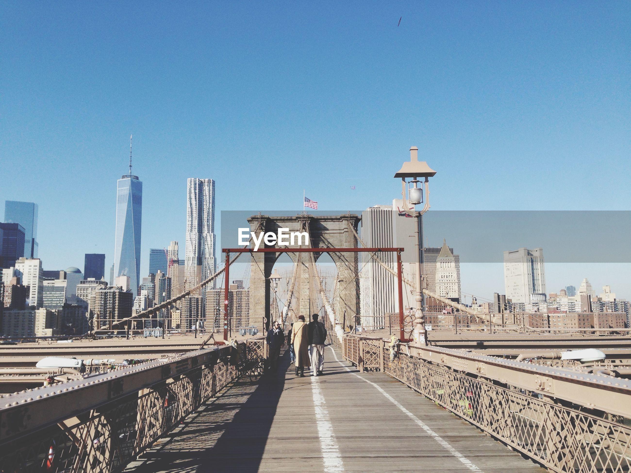 Rear view of people walking on brooklyn bridge by city against clear blue sky
