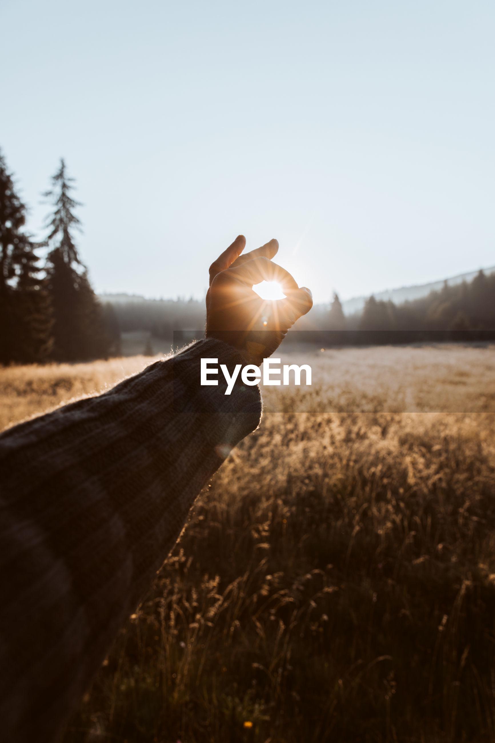 HUMAN HAND HOLDING SUN