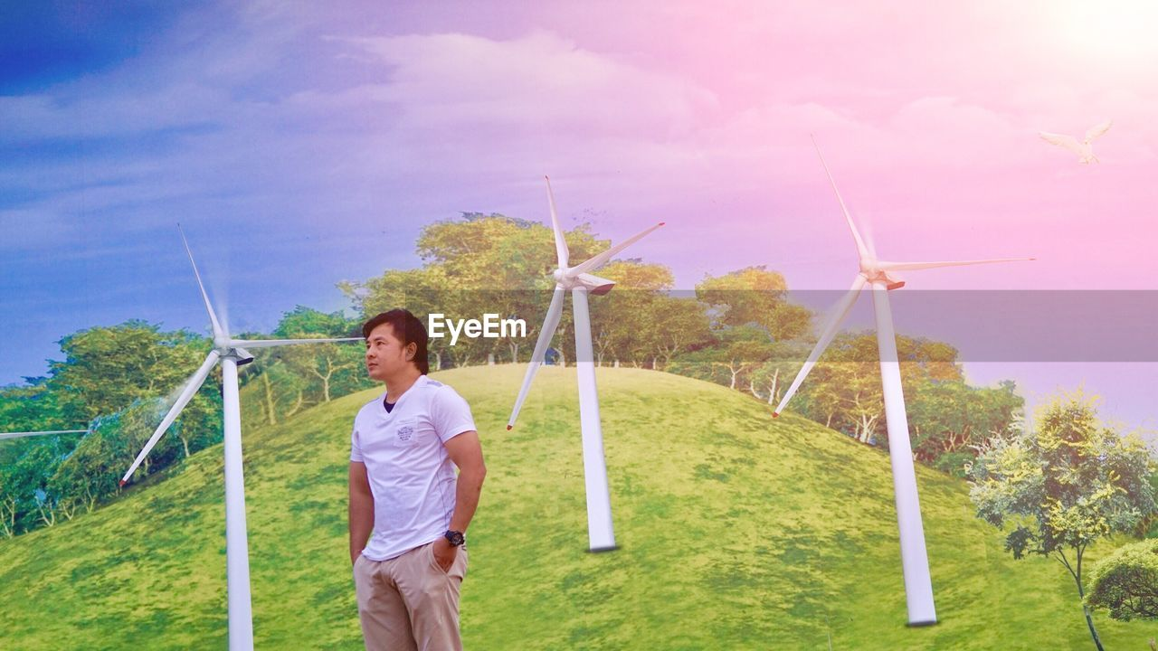 alternative energy, wind turbine, wind power, environmental conservation, renewable energy, fuel and power generation, windmill, casual clothing, choice, one person, nature, field, sky, outdoors, day, technology, industrial windmill, standing, lifestyles, real people, grass, tree, environmentalist, people