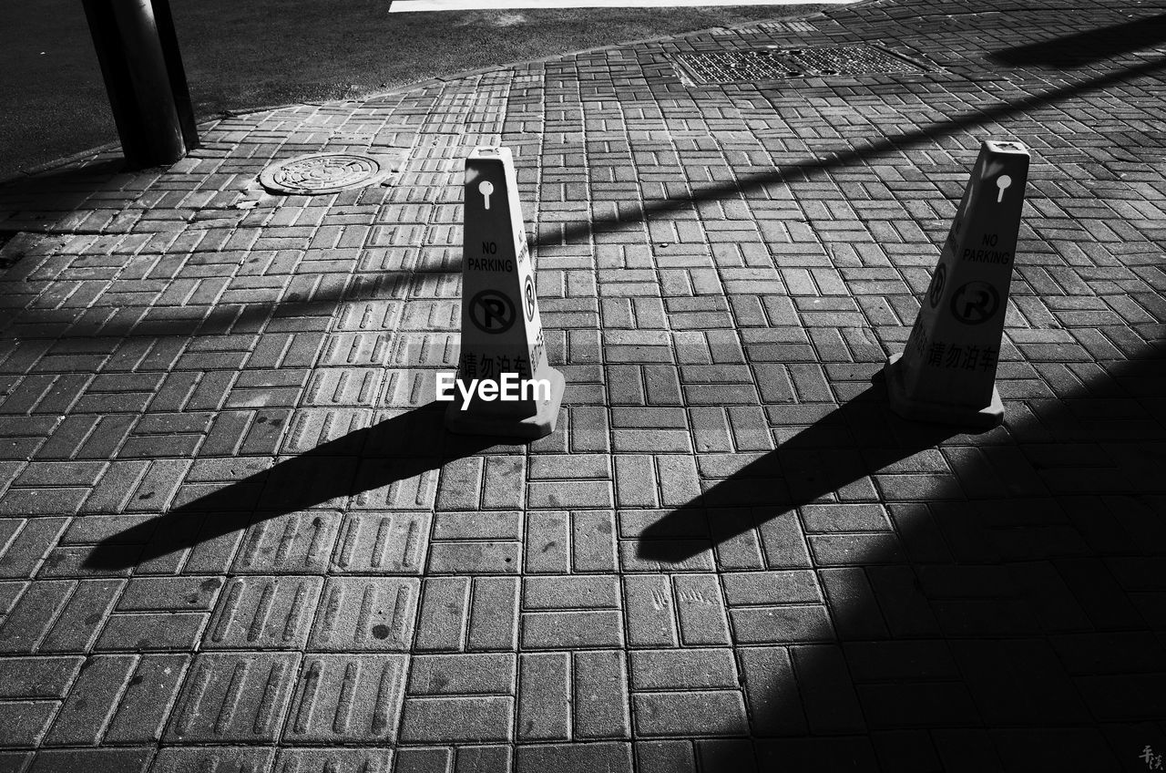 shadow, street, footpath, day, city, sunlight, high angle view, paving stone, outdoors, nature, no people, sidewalk, cobblestone, stone, sign, architecture, metal, communication, focus on shadow, aggression