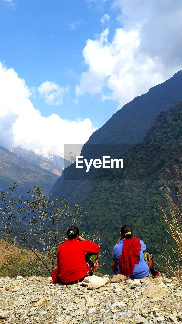 REAR VIEW OF TWO PEOPLE SITTING ON MOUNTAIN AGAINST SKY