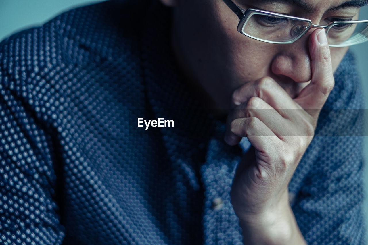 Close-Up Of Worried Mature Man Wearing Eyeglasses