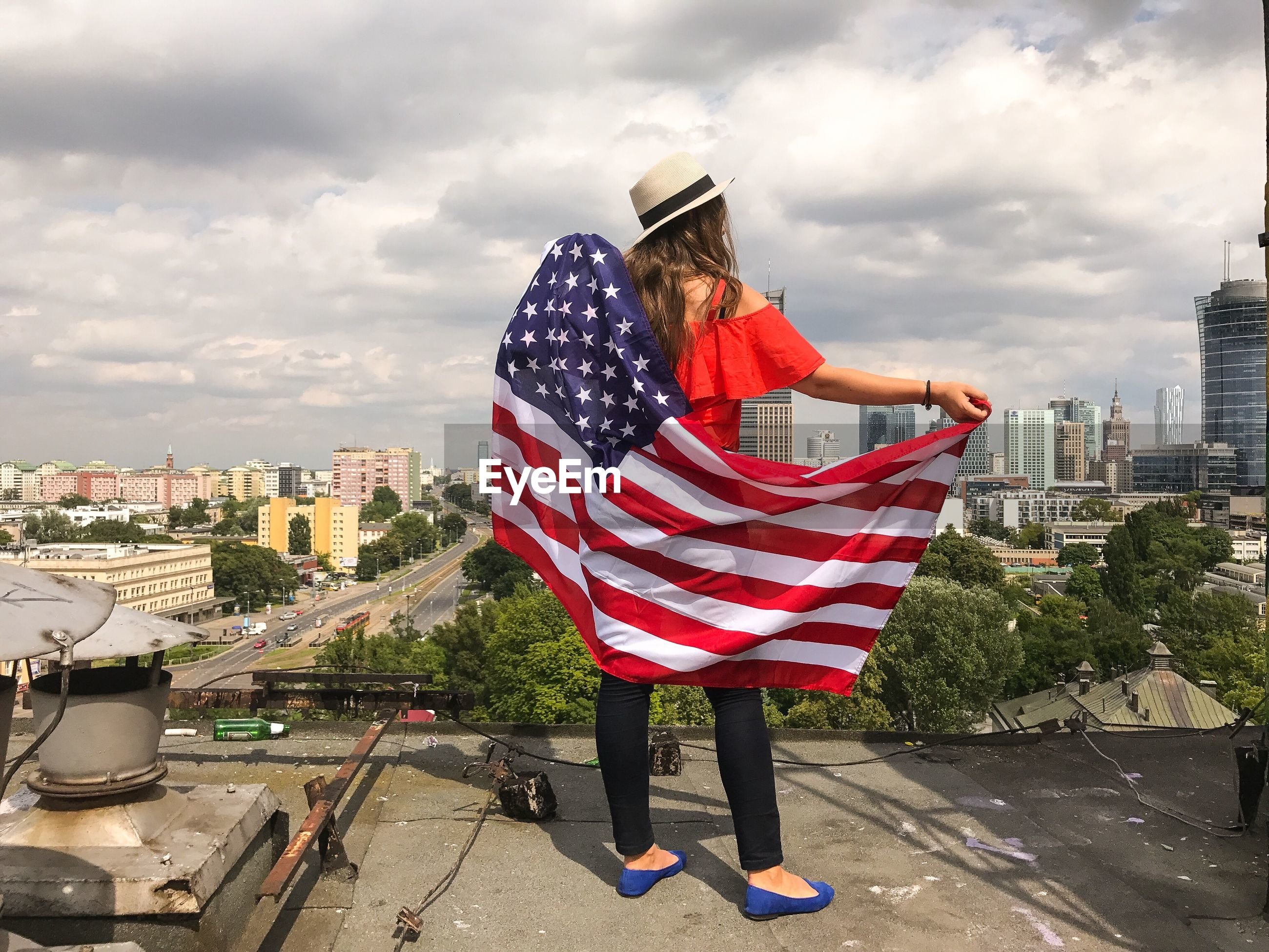 Rear view of woman holding american flag while standing on terrace