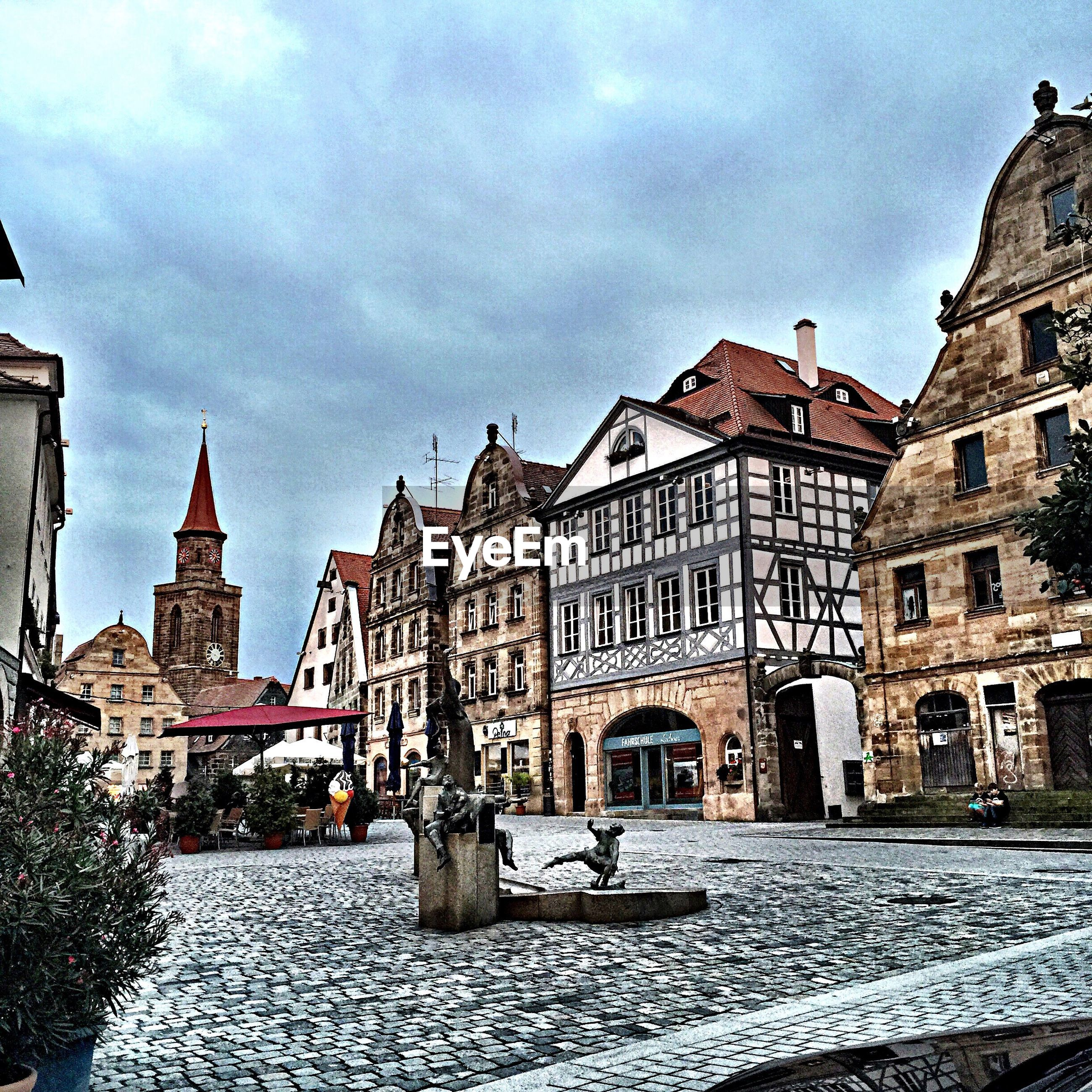 architecture, building exterior, built structure, sky, city, cloud - sky, street, incidental people, cobblestone, building, cloudy, water, old town, transportation, residential building, travel destinations, history, day, city life, cloud